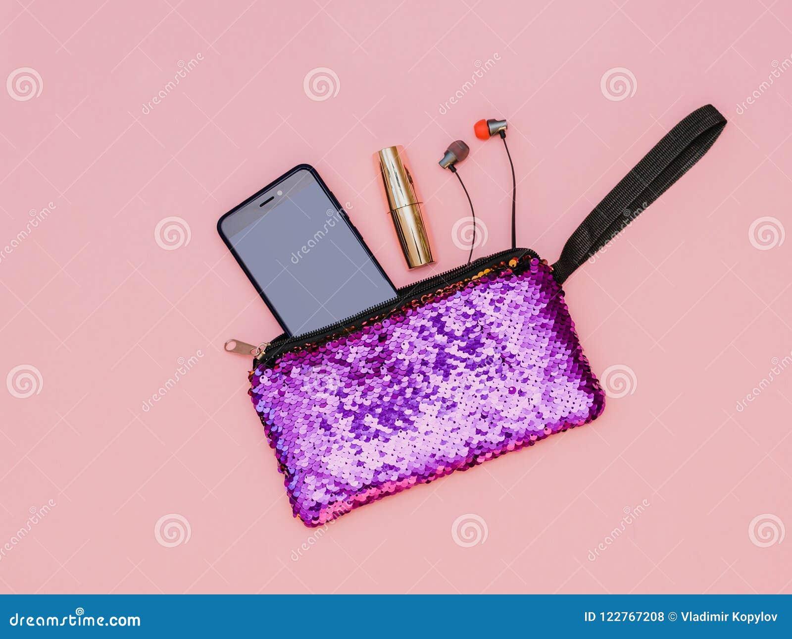 Purpurowa kobiety ` s torebka z telefon pomadką i hełmofony na różowimy stół Pastelowy kolor Mieszkanie nieatutowy