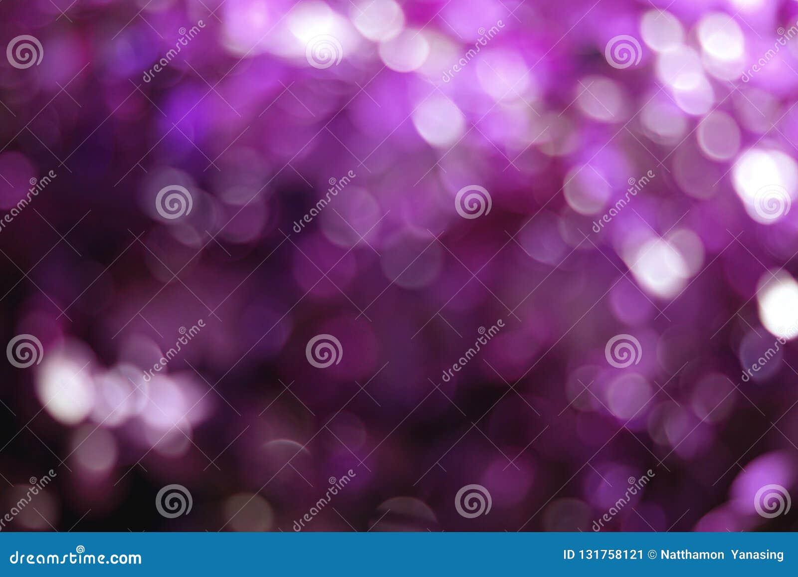 Purpurowy bokeh zaświeca tło, kolorowa błyskotliwość defocused