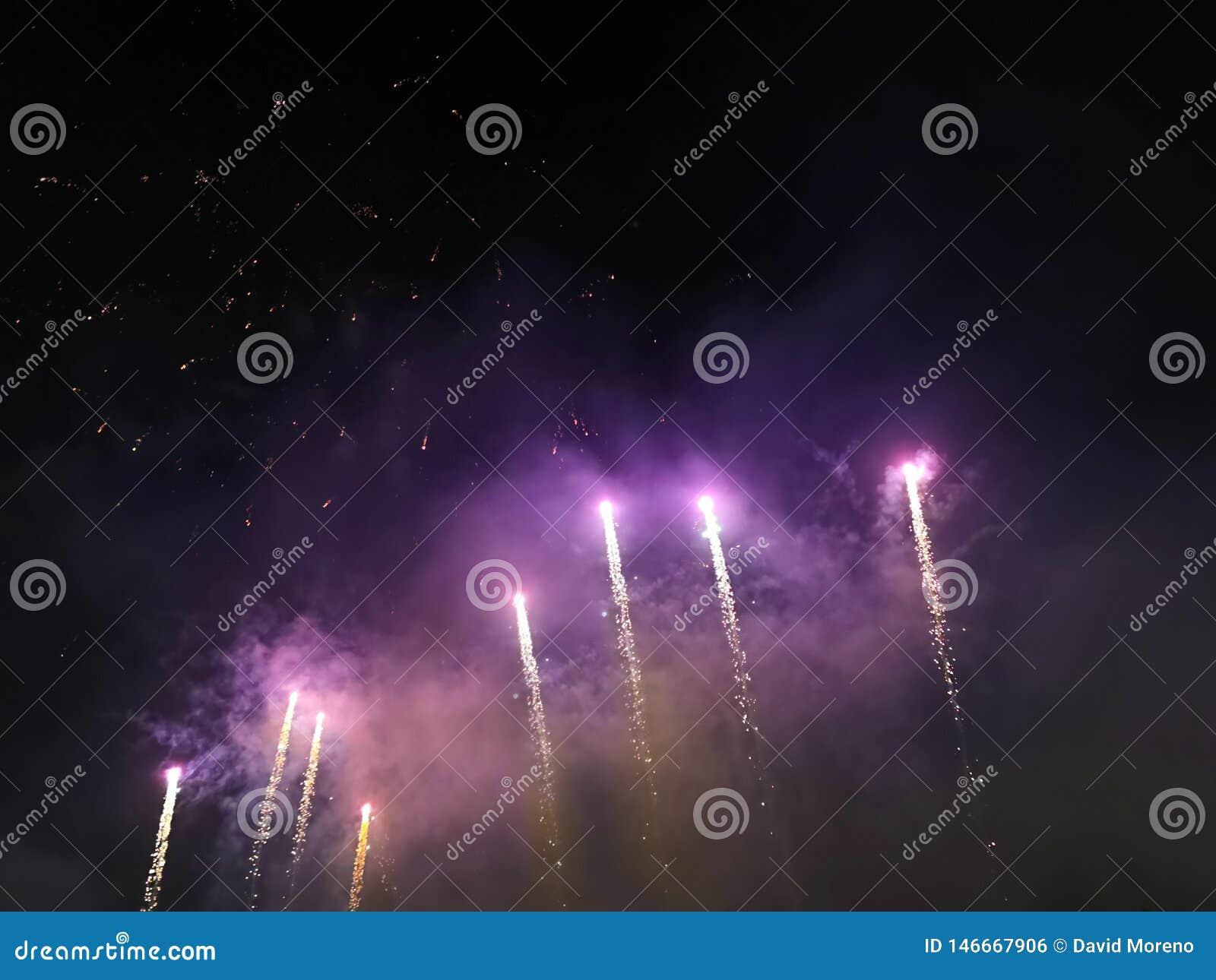 Purpurrote Feuerwerke schleppen im nächtlichen Himmel