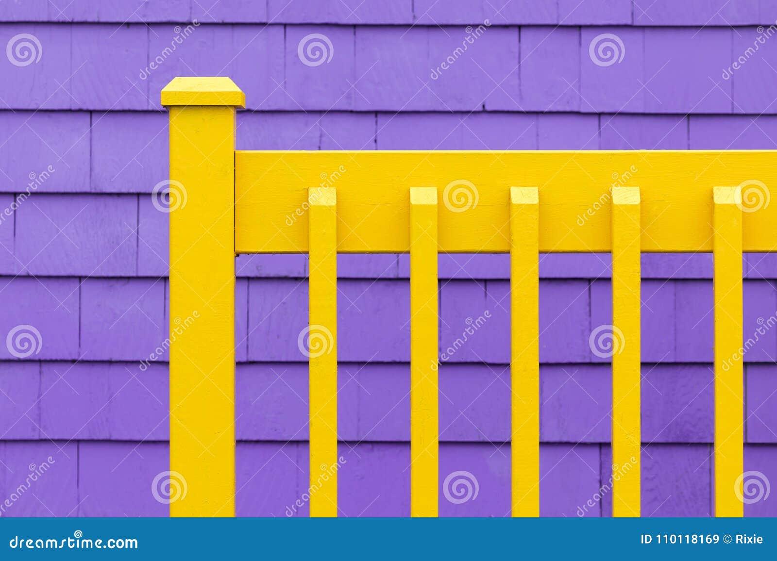Purpurrote Wand und gelber Zaun