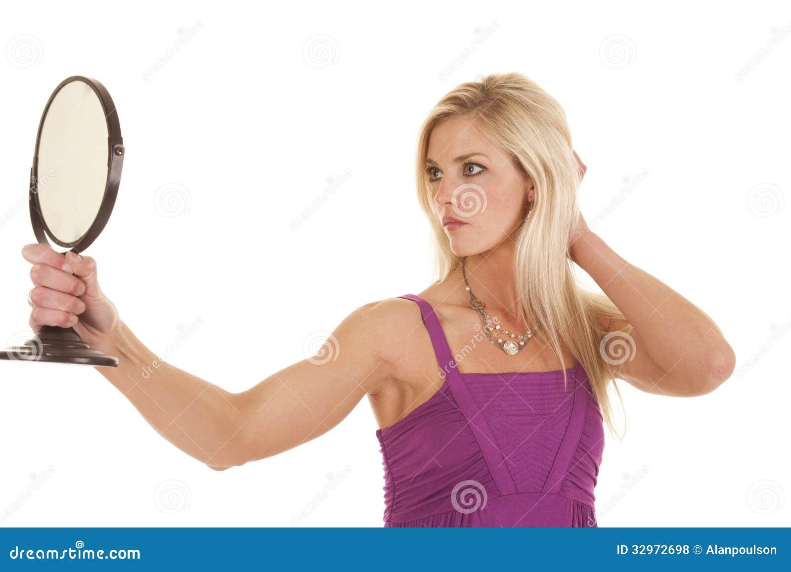 Purpurrotes Schauen der Frau im Spiegel
