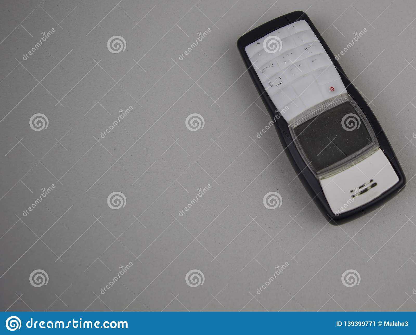 Push-button mobile phone, old on a gray background with free space to fill