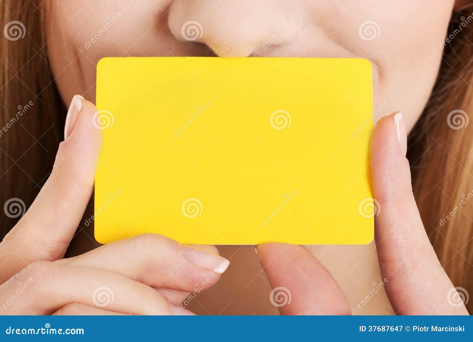 Pusta żółta ogłoszenie towarzyskie karta nad kobiety twarzą.