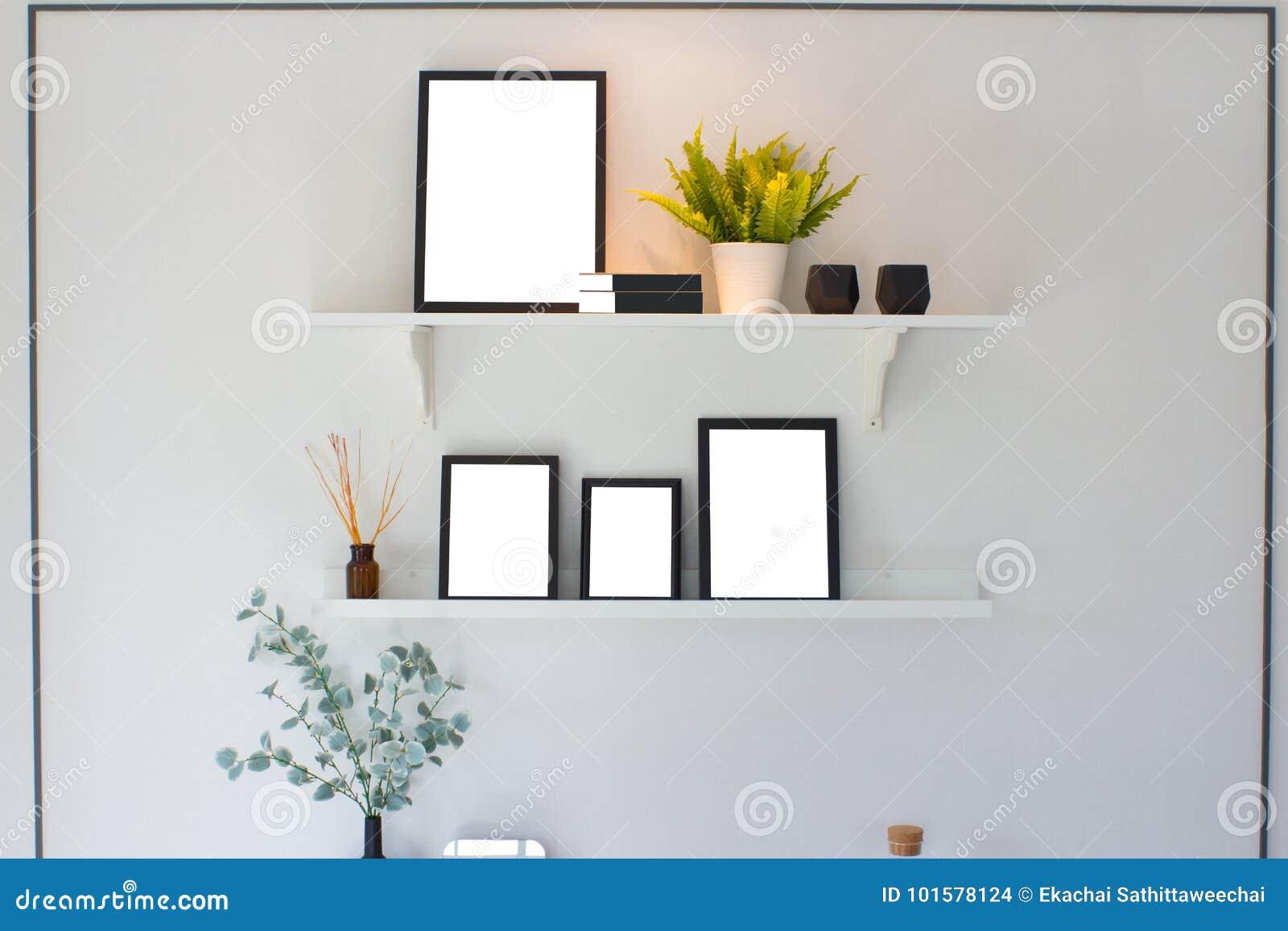 Pusta czarna drewniana rama i drzewo na półce nad białym cementem wal