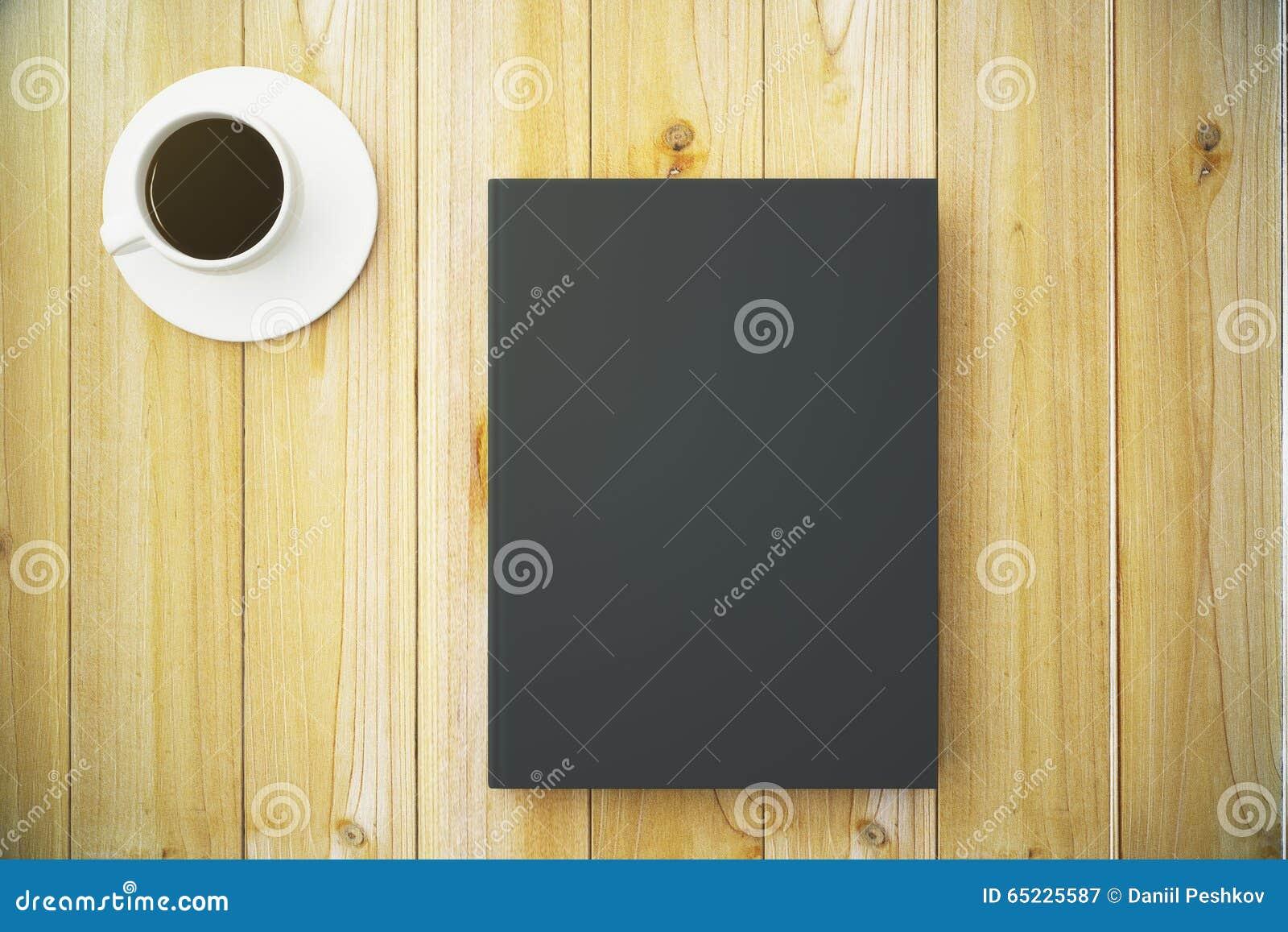 Pusta czarna dzienniczek pokrywa z filiżanką kawy na drewnianym stole