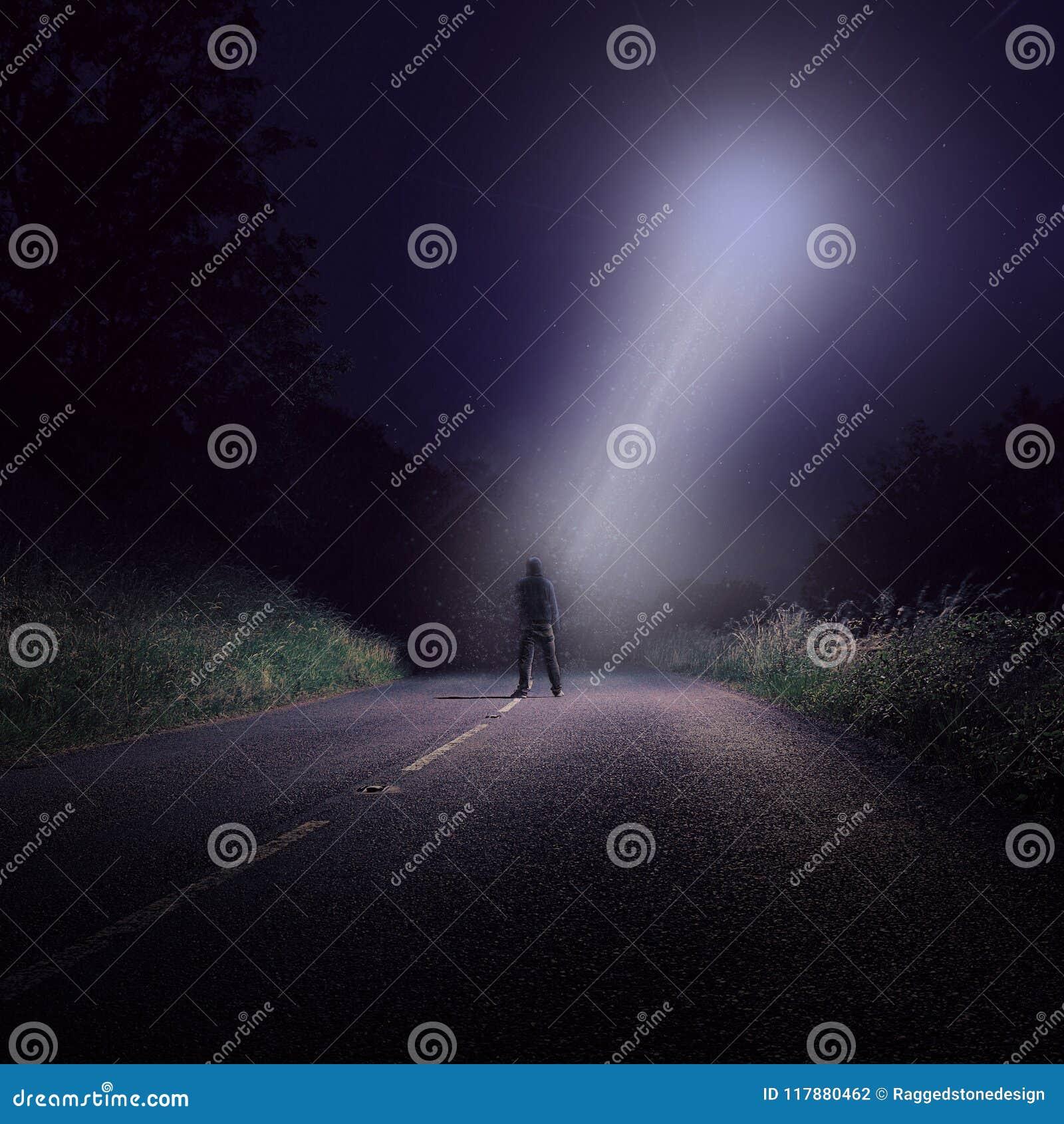 Pusta droga przy nocą z samotną postacią przyglądającą przy jaskrawym UFO z białym promieniem światło nadchodzący puszek up