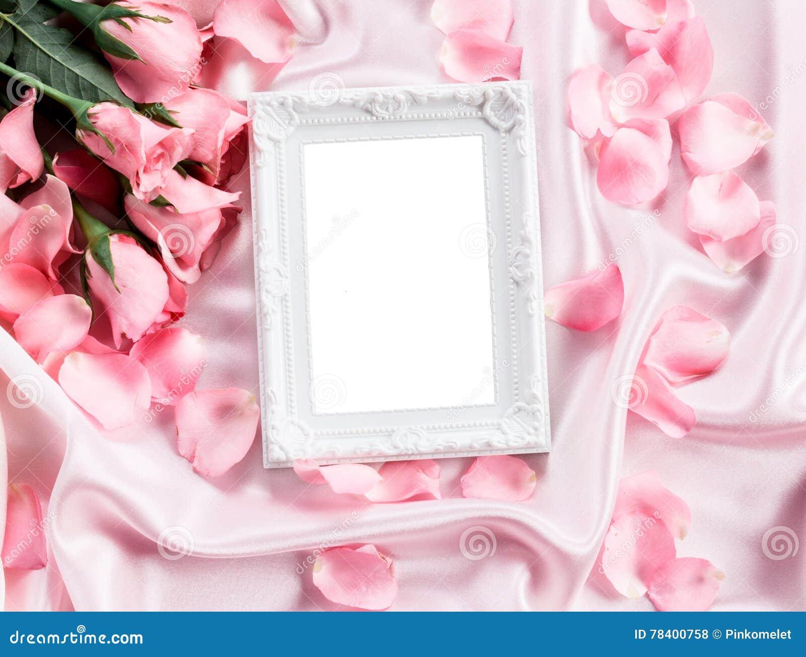 Pusta fotografii rama z bukieta cukierki menchii róż płatkiem na miękkich części menchii jedwabniczej tkaninie, romansie i miłośc