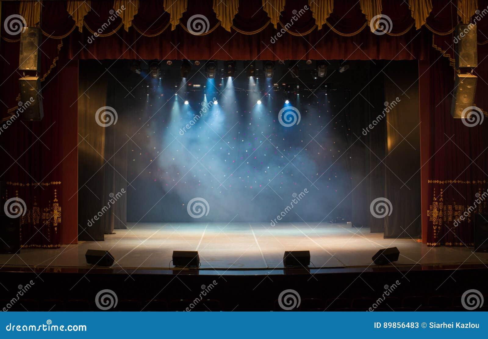 Pusta scena teatr, zaświecająca światłami reflektorów i dymem
