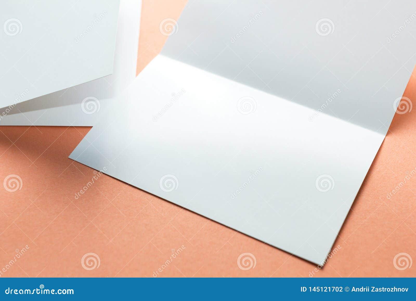 Puste miejsce li?cia kwadratowe broszurki odizolowywa? na pomara?czowym tle Przestrze? dla teksta