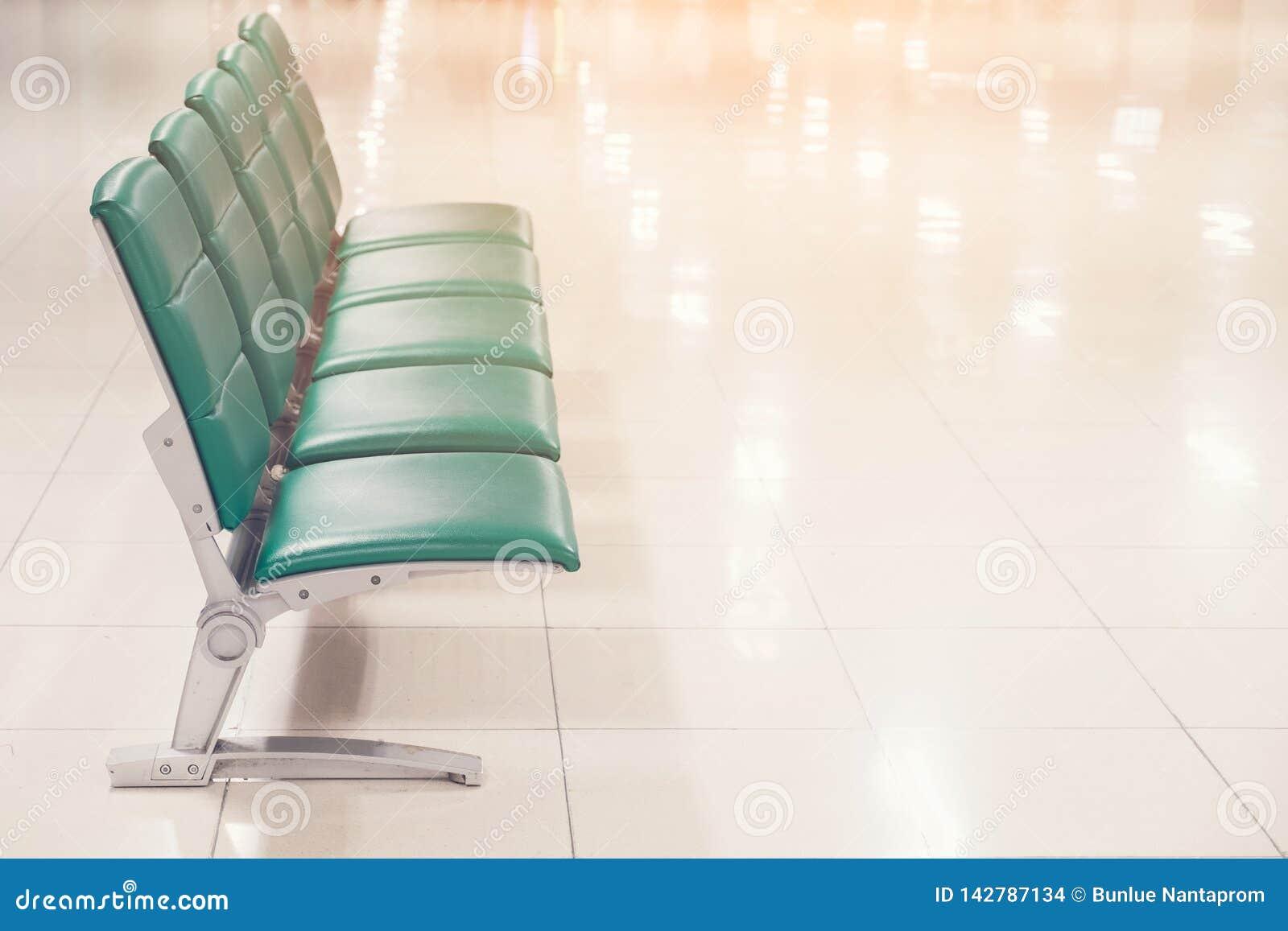 Puste siedzenia przy biznesem lub krzesłami są zielonym skórą z metal nogami i żadny podłokietnika czekania terenem
