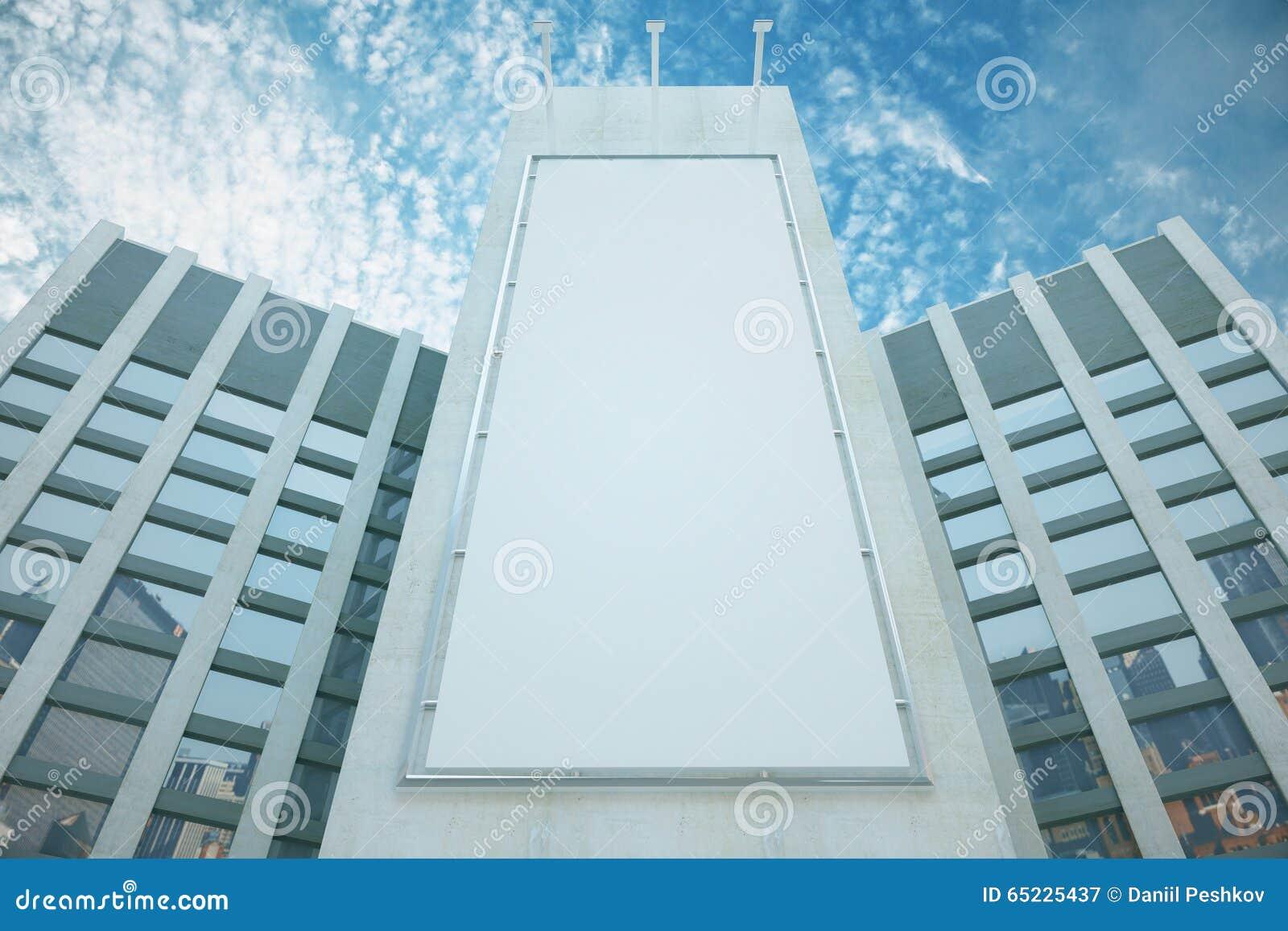Pusty biały billboard wśród drapaczy chmur z niebieskim niebem