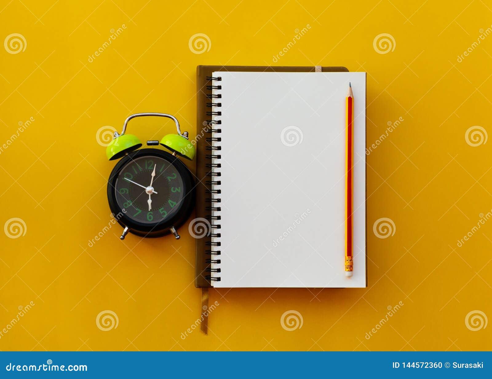 Pusty biały notepad z ołówkiem i budzikiem na żółtym tle