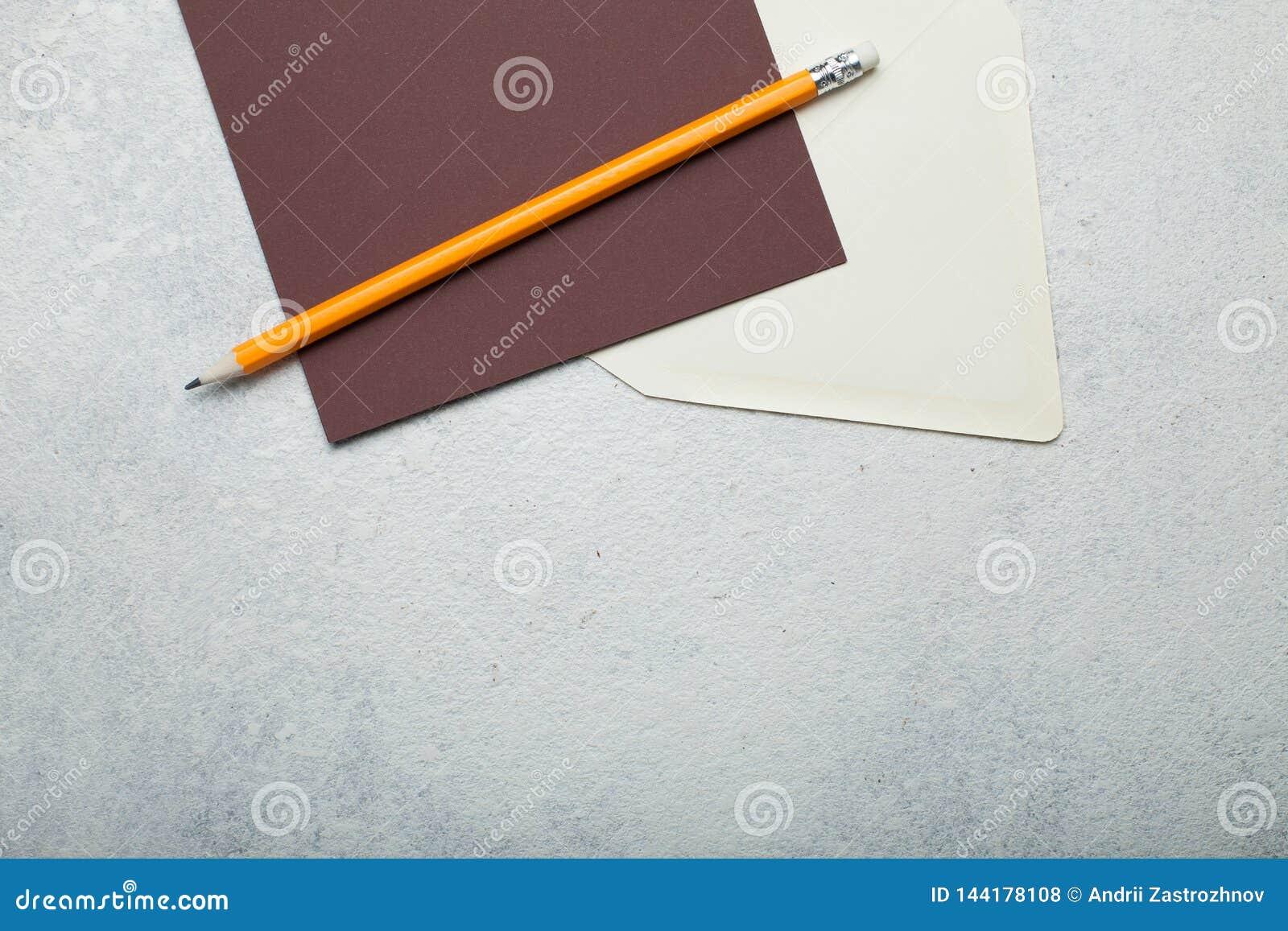 Pusty brązu kwadrata kawałek papieru, beżowa koperta i ołówek na rocznika bielu tle, Opr??nia przestrze? dla teksta