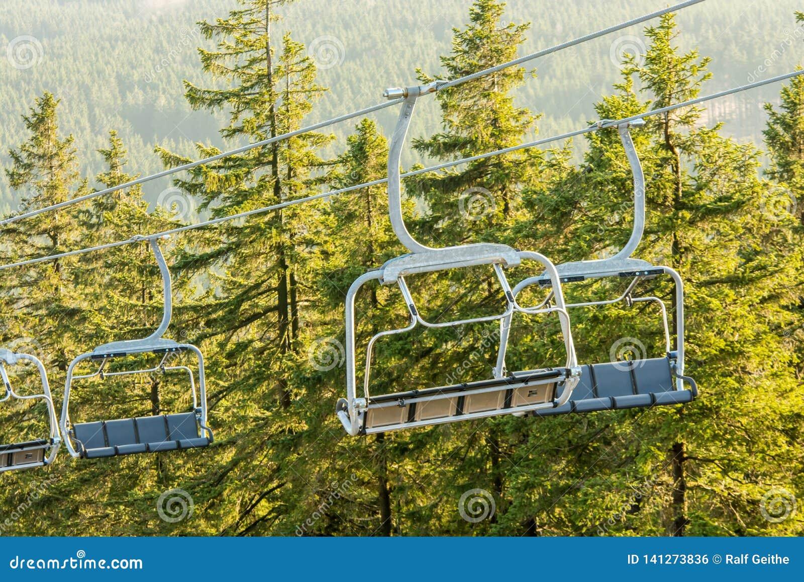 Pusty chairlift z dużymi gondolami w lasowym terenie
