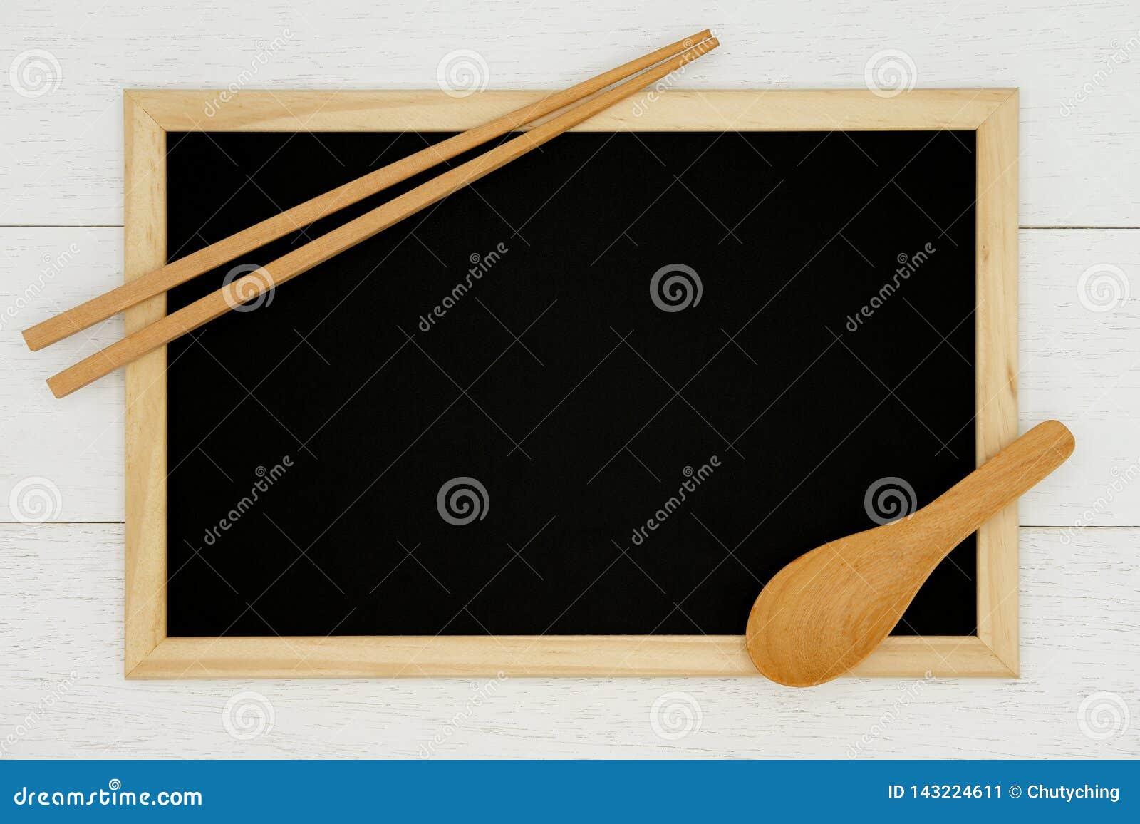 Pusty chalkboard z drewnianą łyżką i chopstick na białym drewnianym deski tle
