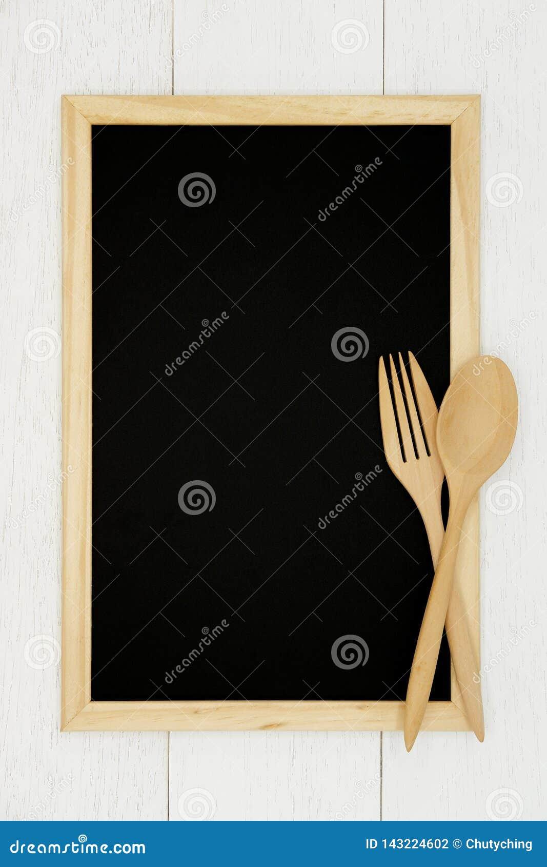 Pusty chalkboard z drewnianą łyżką i rozwidlenie na białym drewnianym deski tle