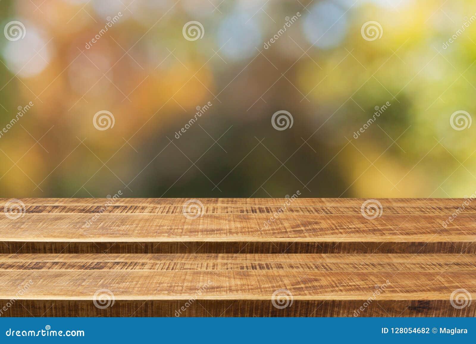 Pusty drewniany kroka stół z nadmiernym jesieni natury bokeh tłem