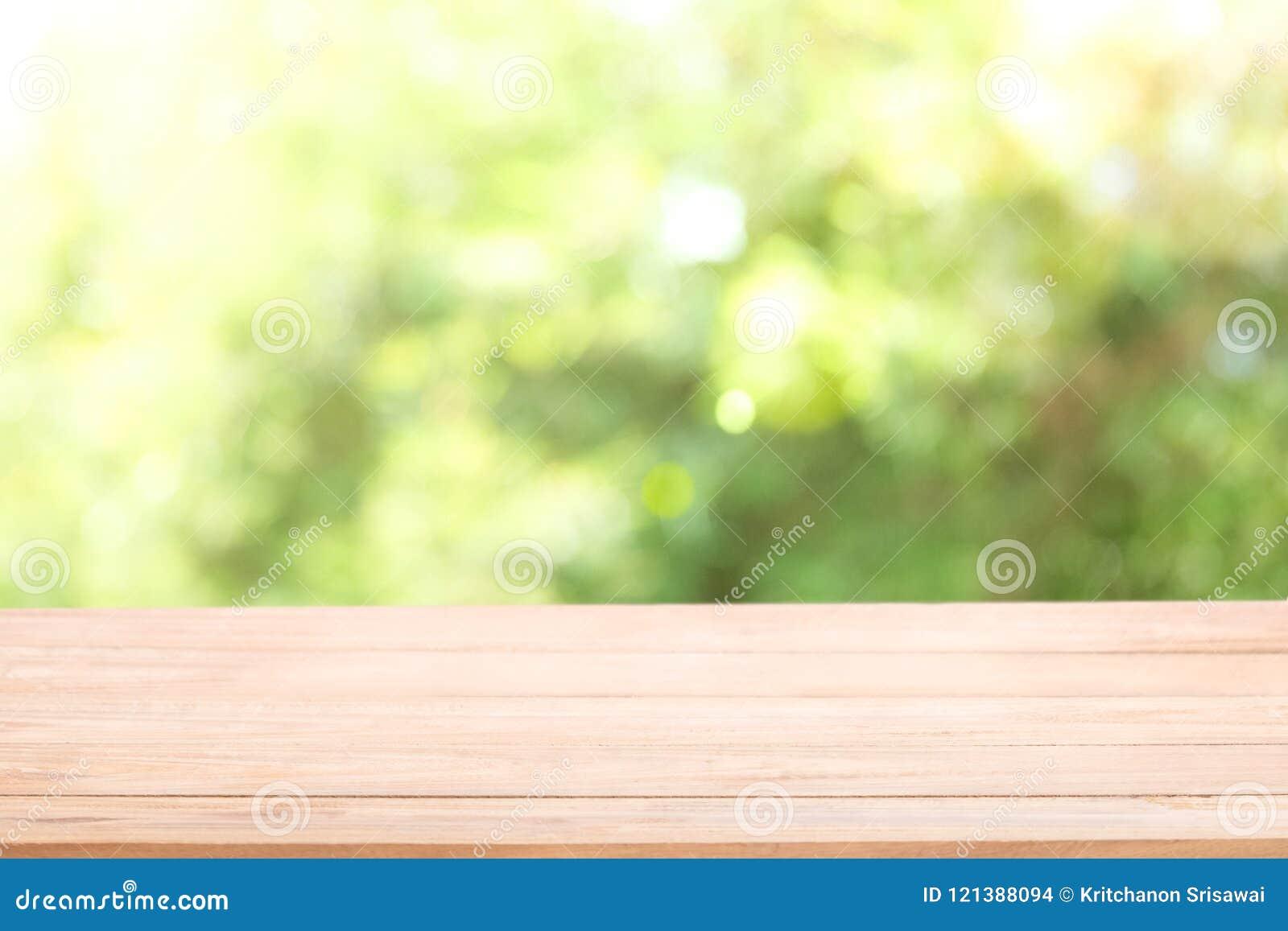 Pusty drewniany stołowy wierzchołek z słońcem i plamy zielonym drzewem