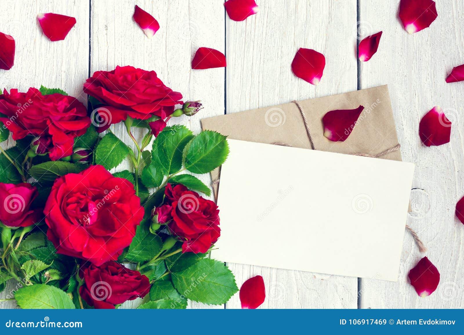 Pusty kartka z pozdrowieniami i koperta z czerwonych róż płatkami i kwiatami