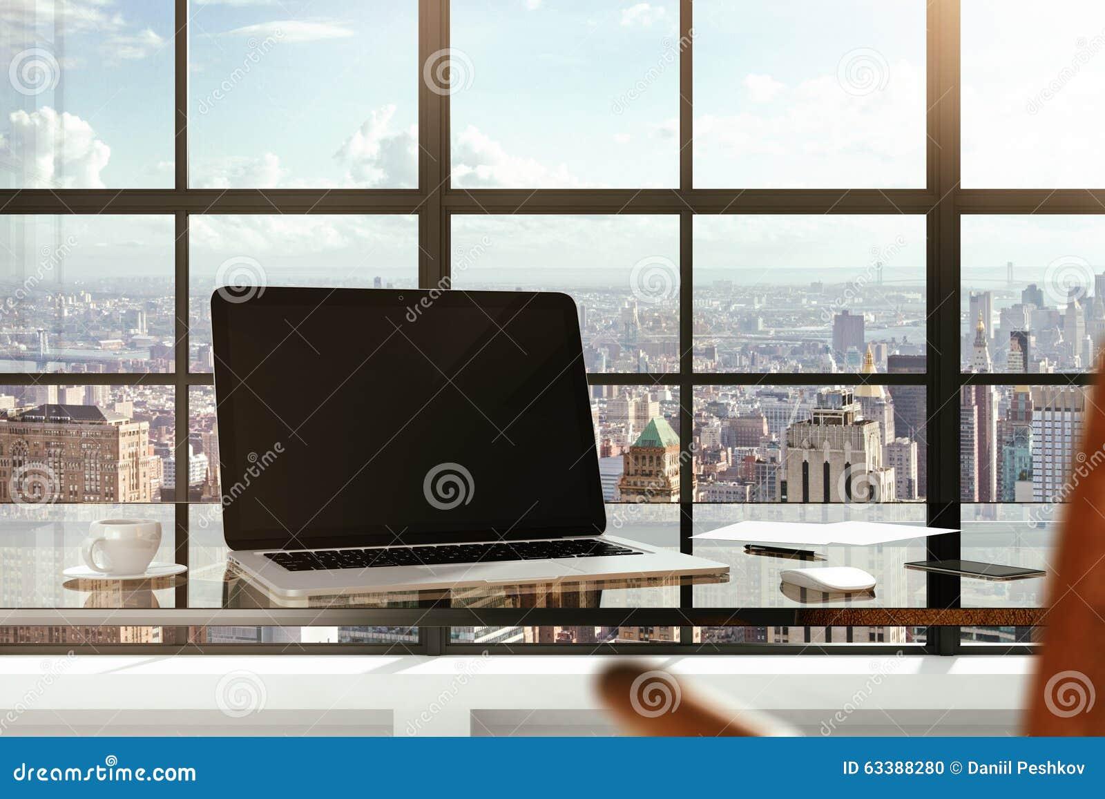 Pusty laptop na szklanym stole w nowożytnego biura i miasta widokach