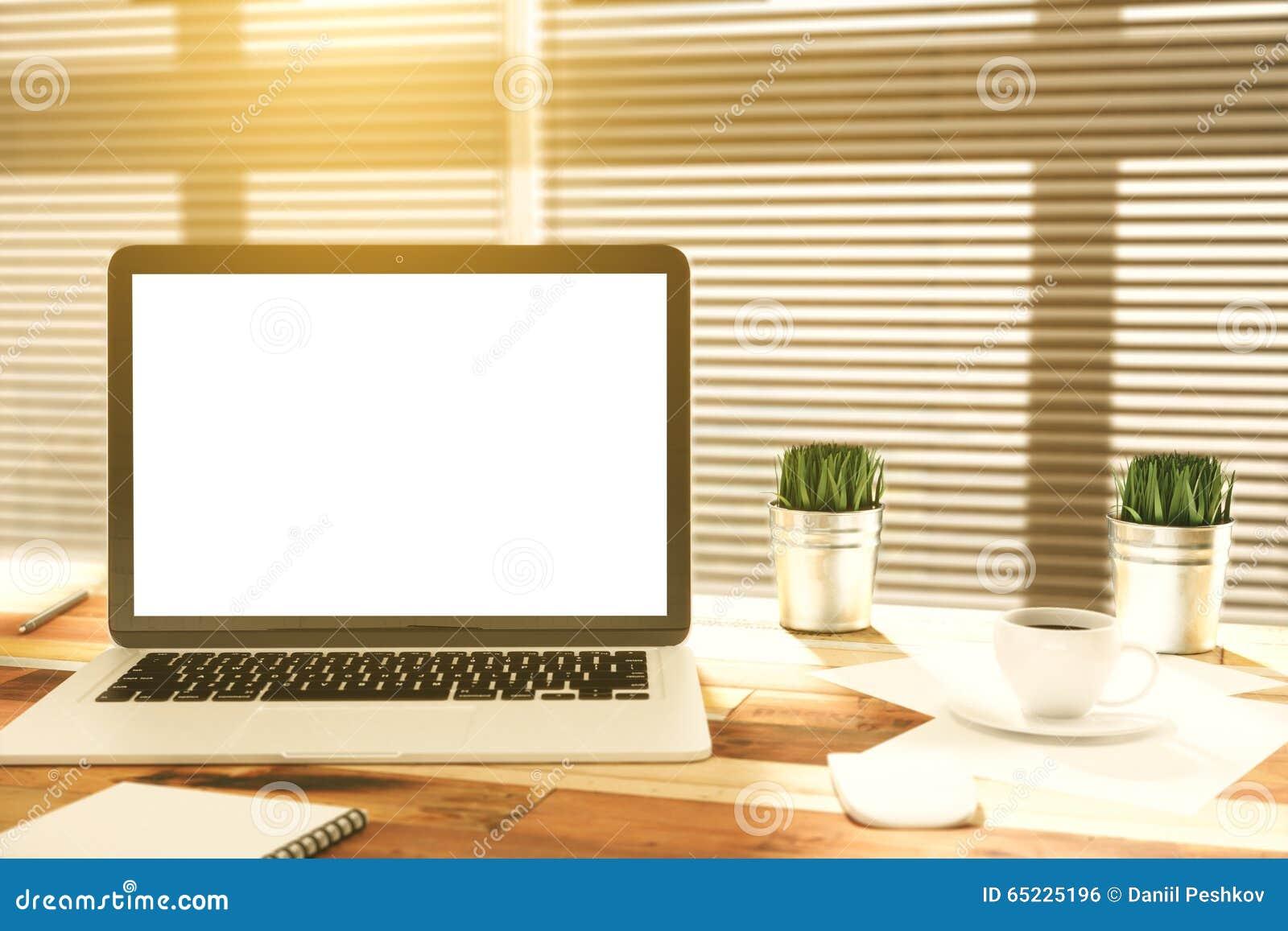 Pusty laptopu ekran na drewnianym stole z filiżanką kawy i trawą