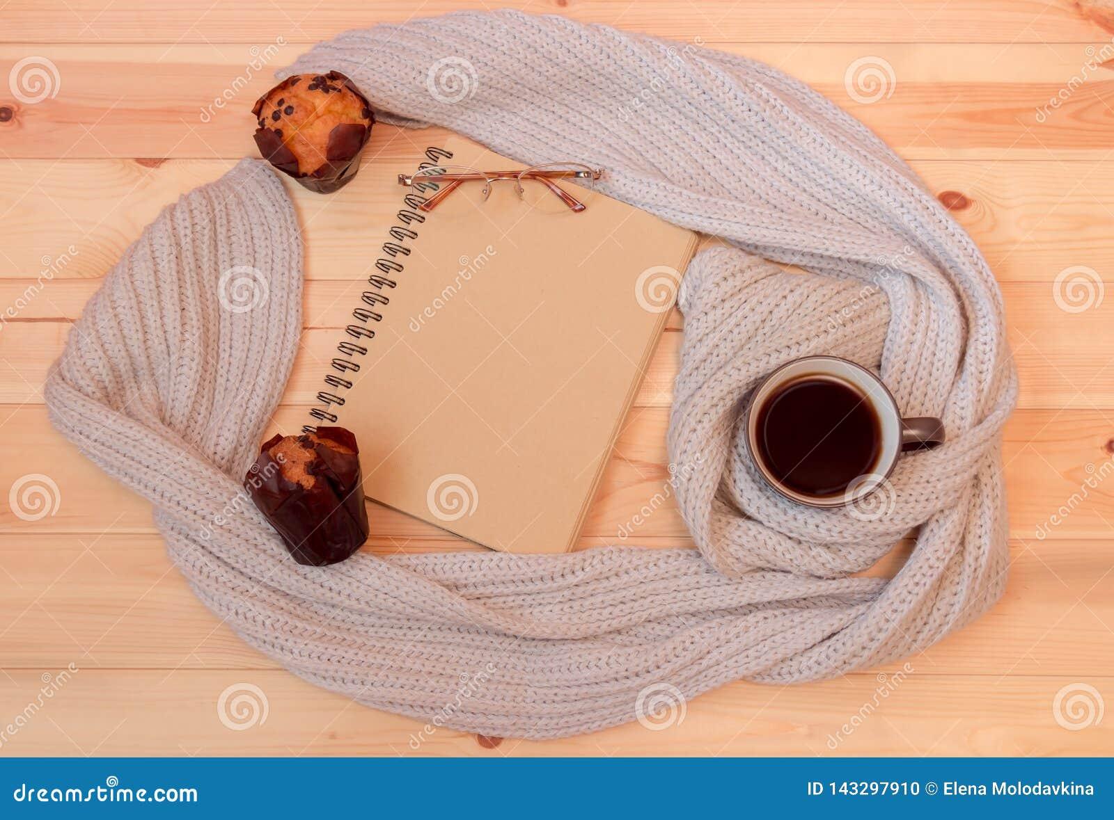Pusty notatnik, kubek zawijający w szaliku gorąca kawa, szkła i słodka bułeczka,
