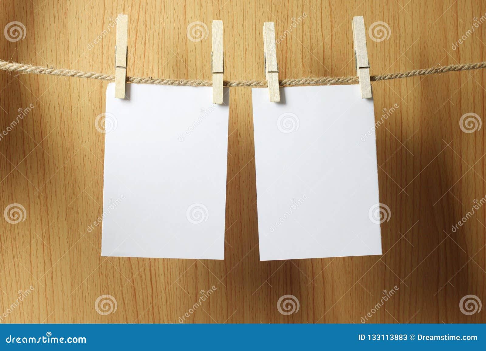 Pusty papier wiesza na brąz arkanie z Drewnianymi papierowymi klamerkami na w