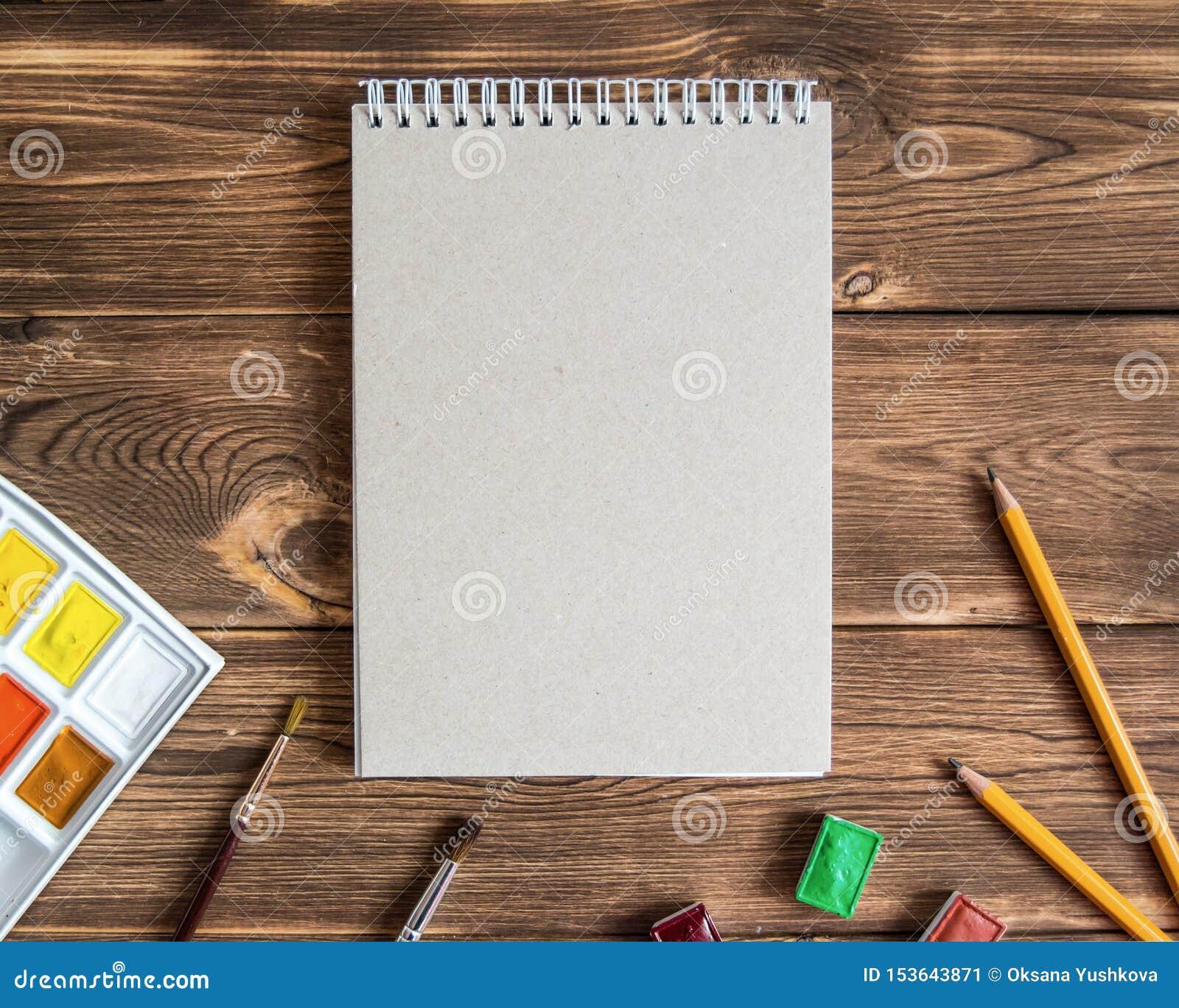 Pusty rysunku ochraniacz z ołówkami i farbami na drewnianym tle