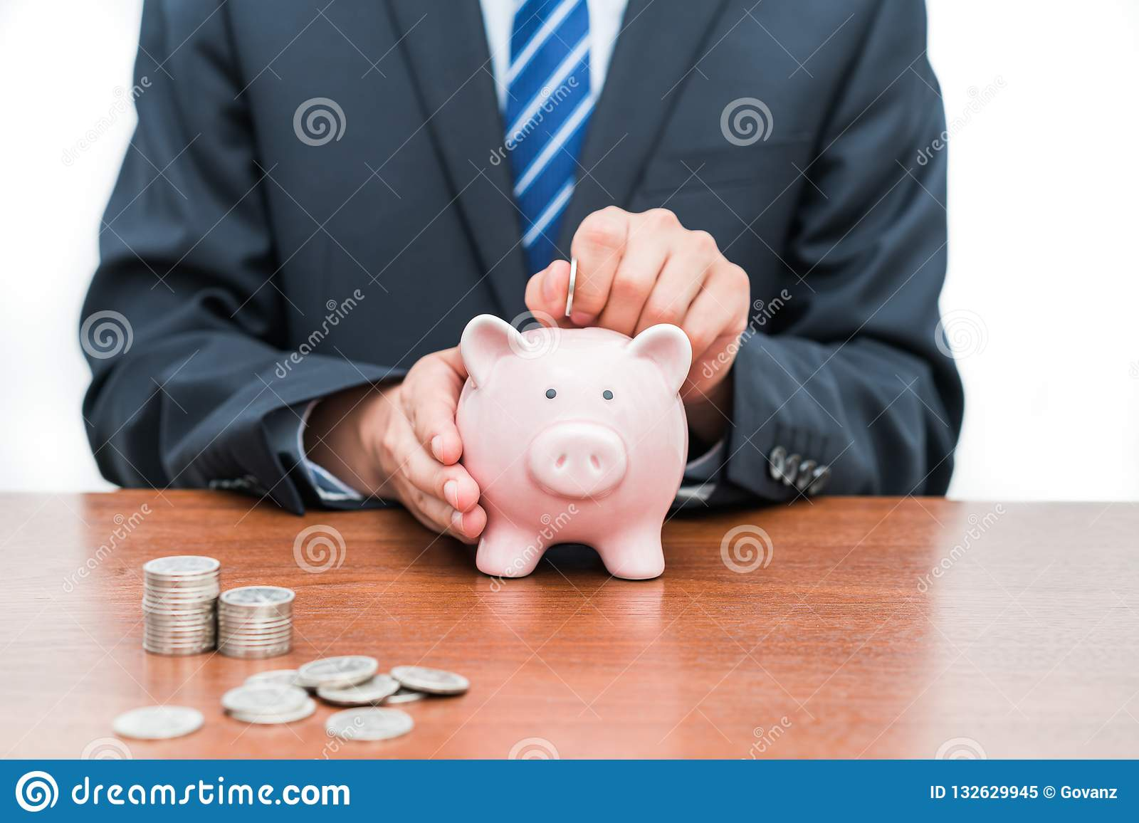 Putting coins into piggy Bank-The concept of savings