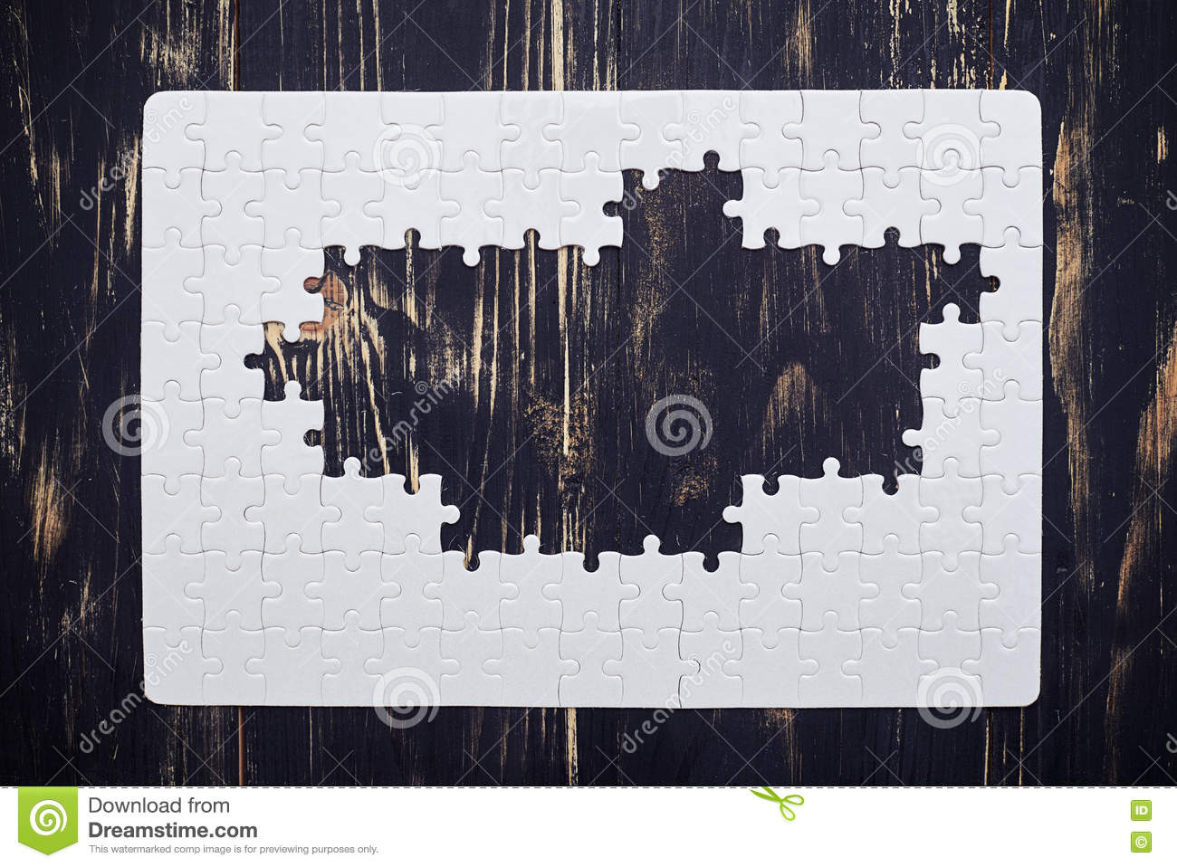 Puzzle without middle part on dark wooden desk