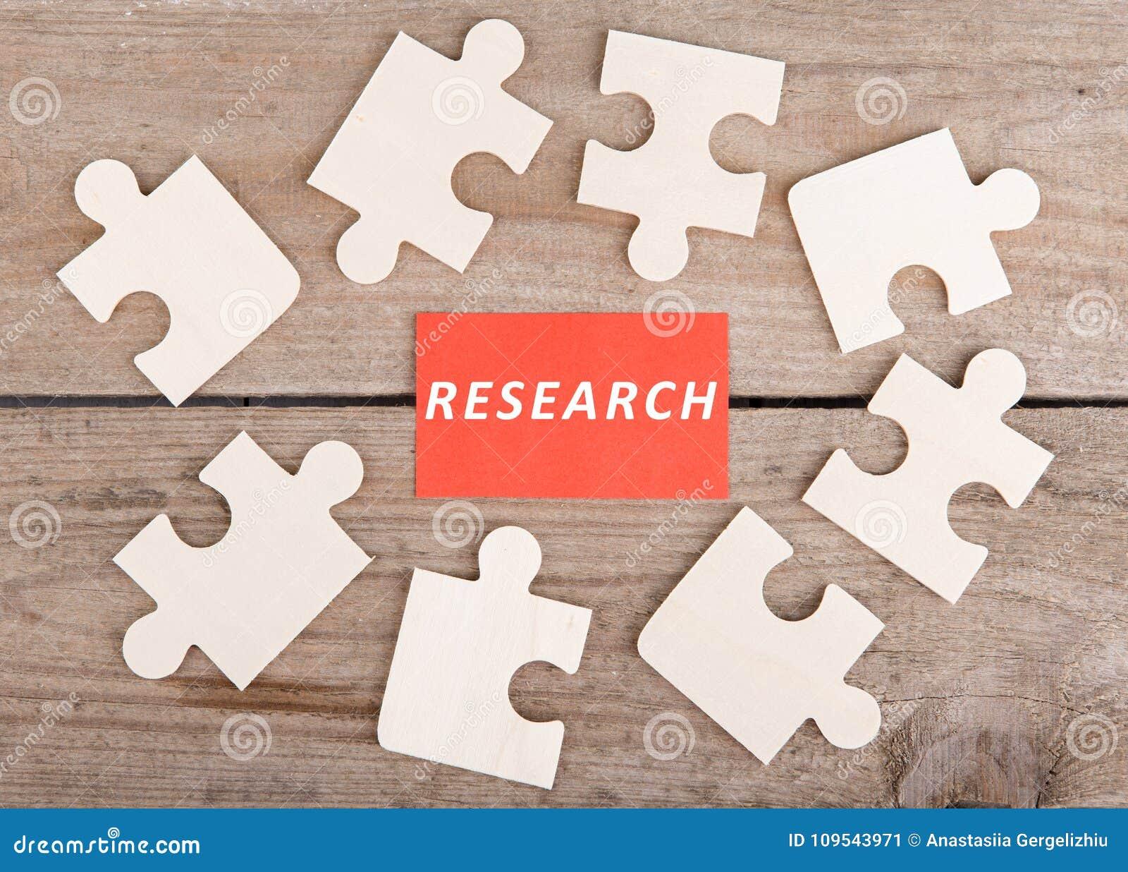 Puzzle-Stücke mit Text u. x22; Research& x22; auf hölzernem Hintergrund