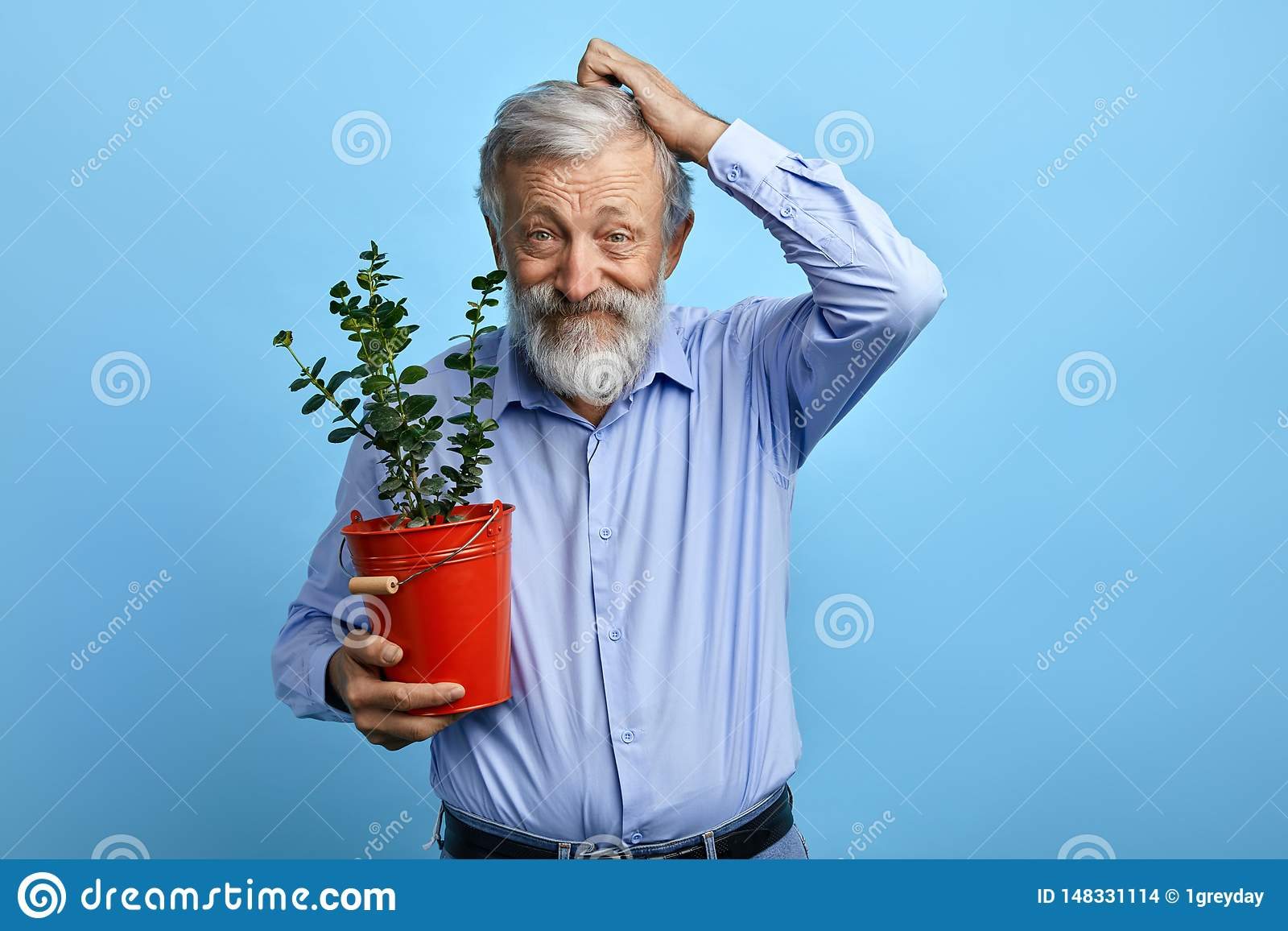 Puzzled funny old man scratching his hair while posing to the camera