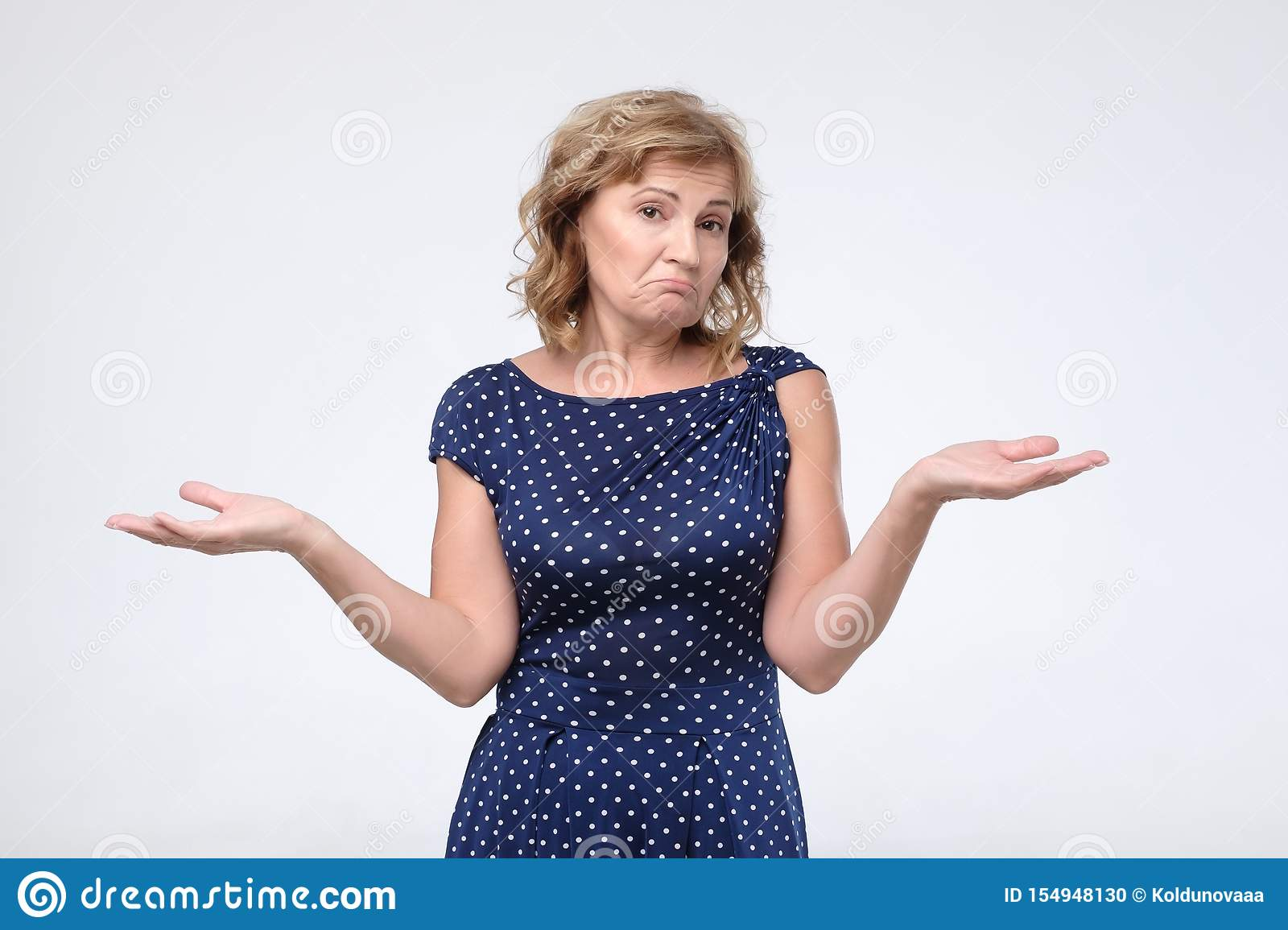 Puzzled mature female in blue dress shrugs shoulders as does not know answer