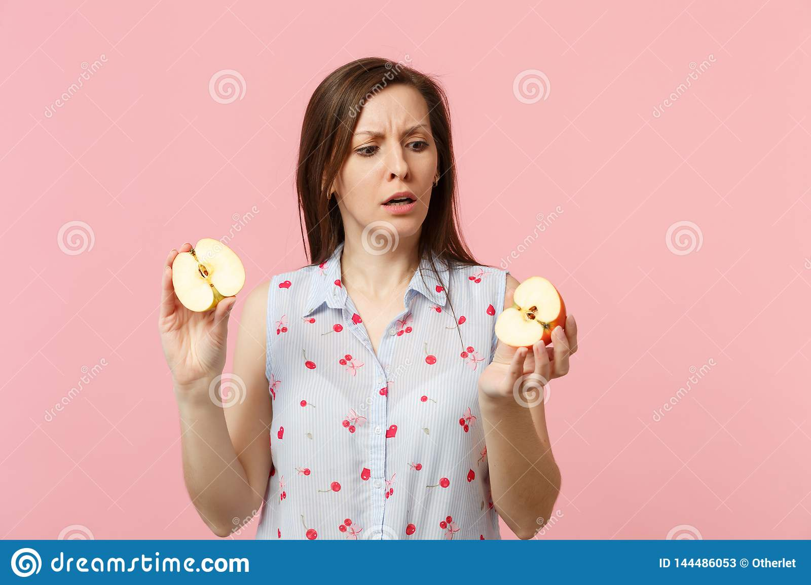 Puzzled young woman in summer clothes holding in hands halfs of fresh ripe apple fruit isolated on pink pastel