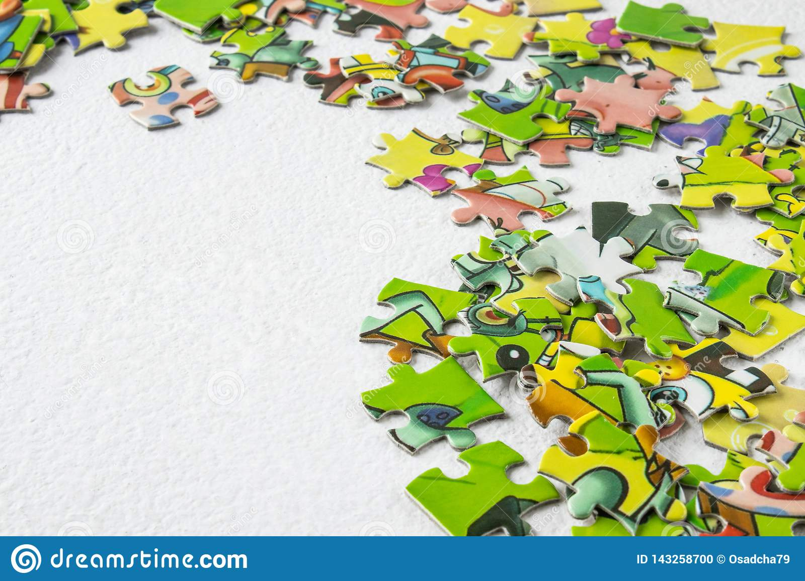 Puzzles scattered on a light table with the right close-up. Educational game for children and adults. Copy Space