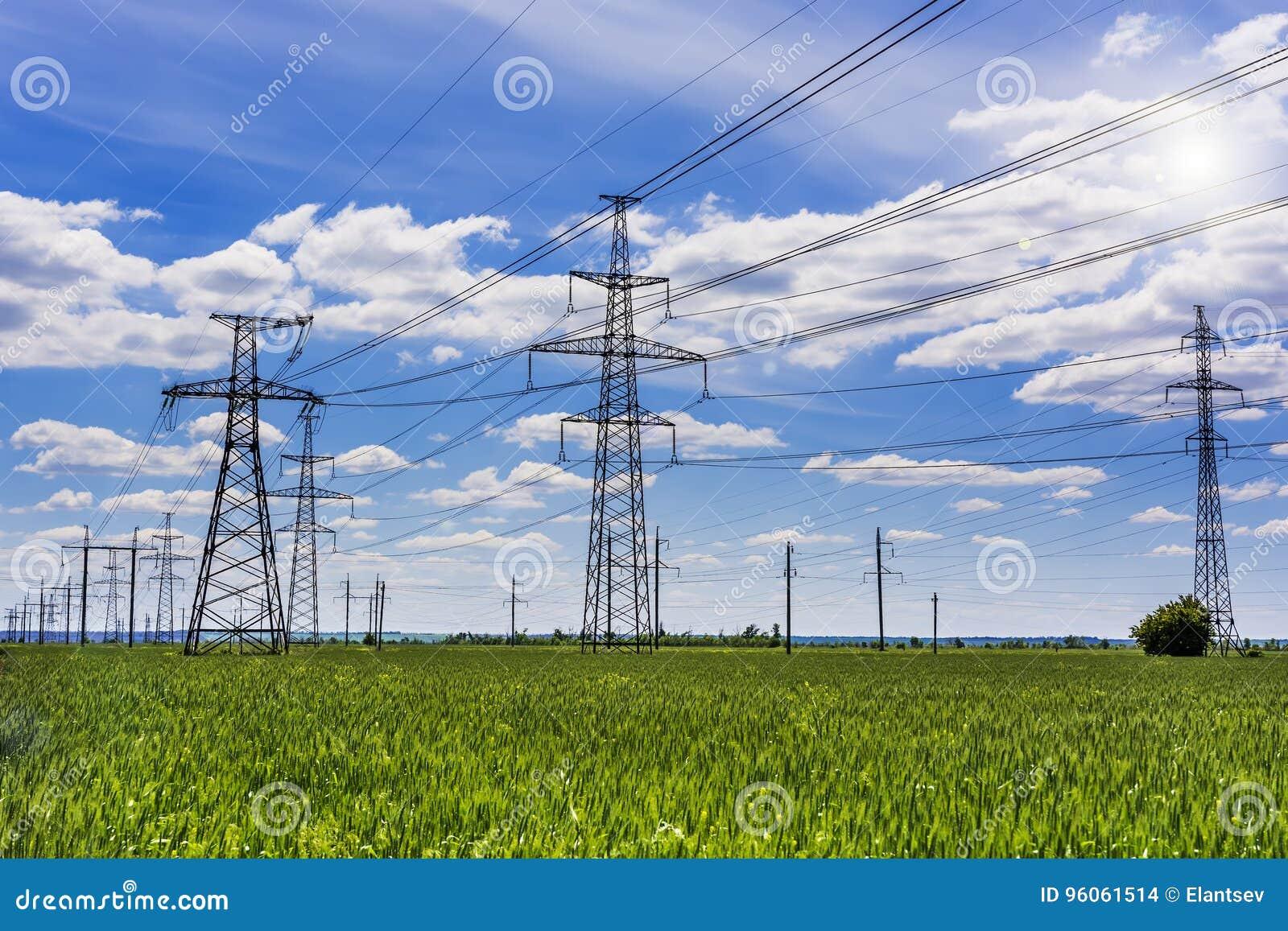 Pylônes de l électricité entrant dans la distance au-dessus de la campagne d été