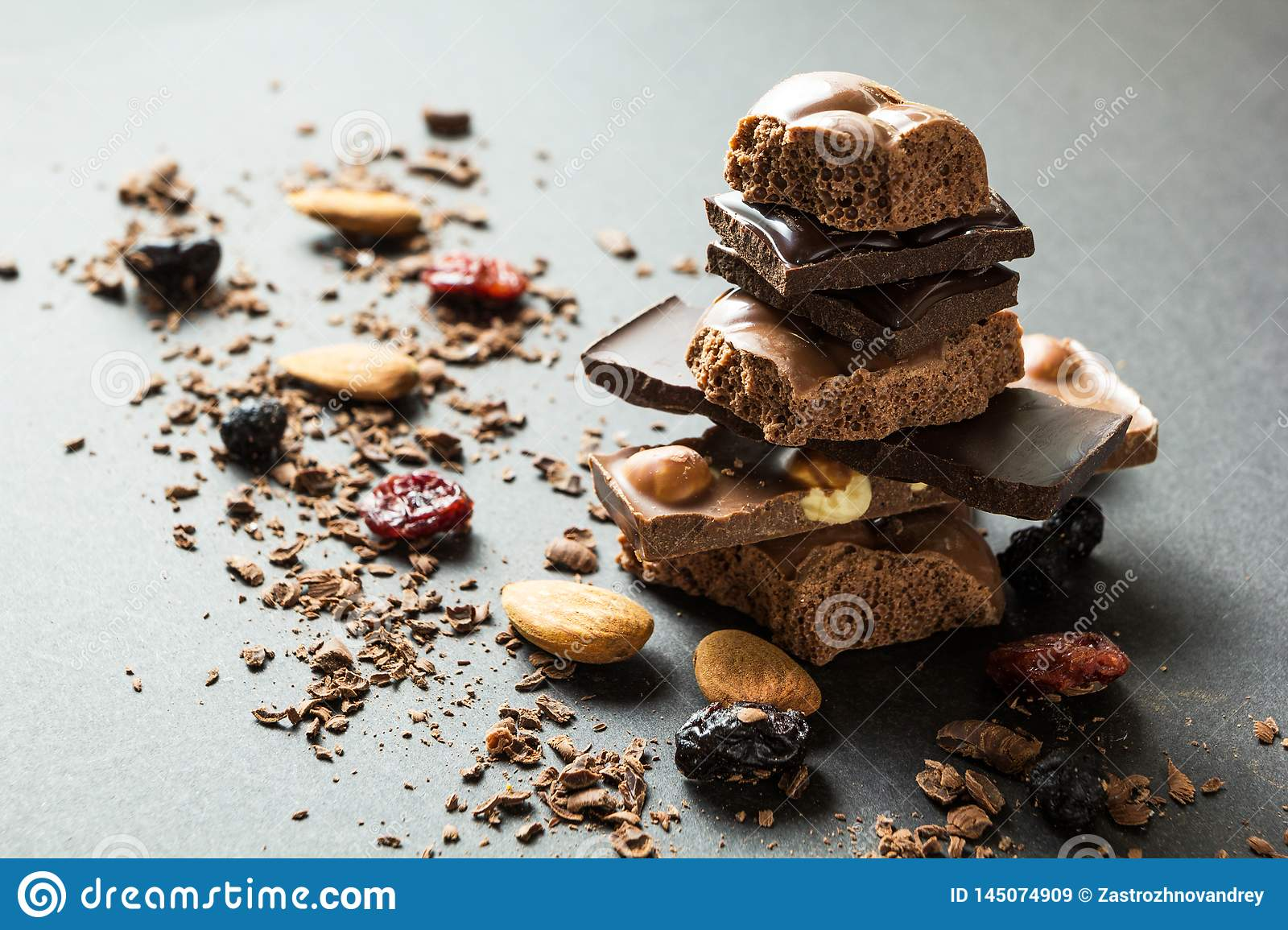 Pyramid of chocolate and dried fruits on a black background