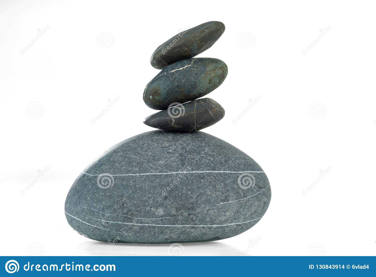 A pyramid of four stones in balance is isolated on a white background