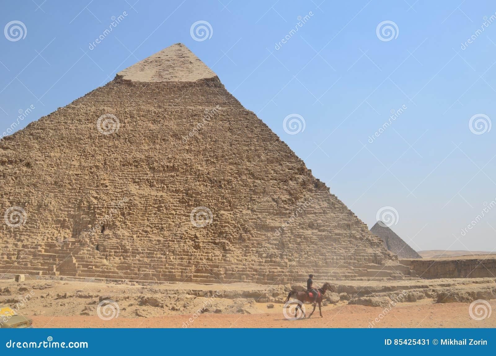 Pyramid i sanddamm under gråa moln