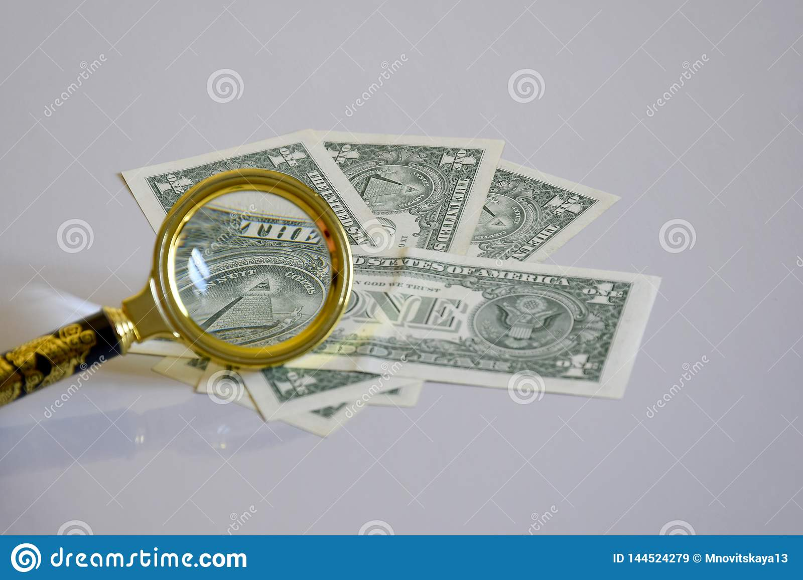 Pyramid of one-dollar banknote inside a magnifying glass