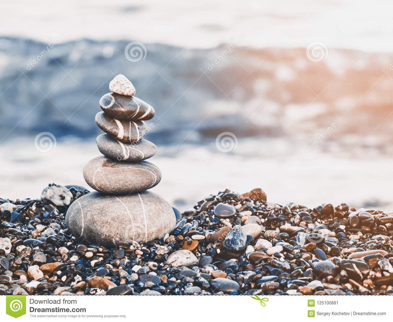 Pyramid of pebbles on the beach.Waves in background. Retro style.