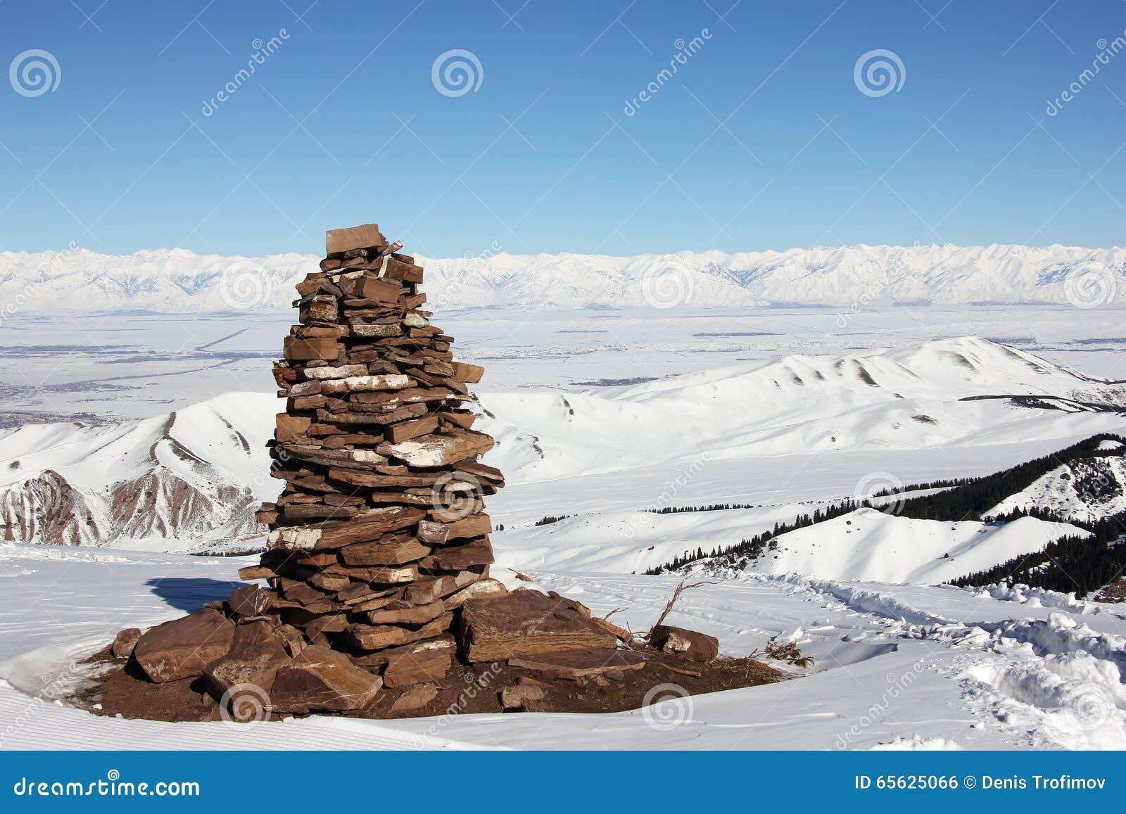 Pyramide en pierre sur le dessus de la montagne, vue sur le lac Issyk Kul val