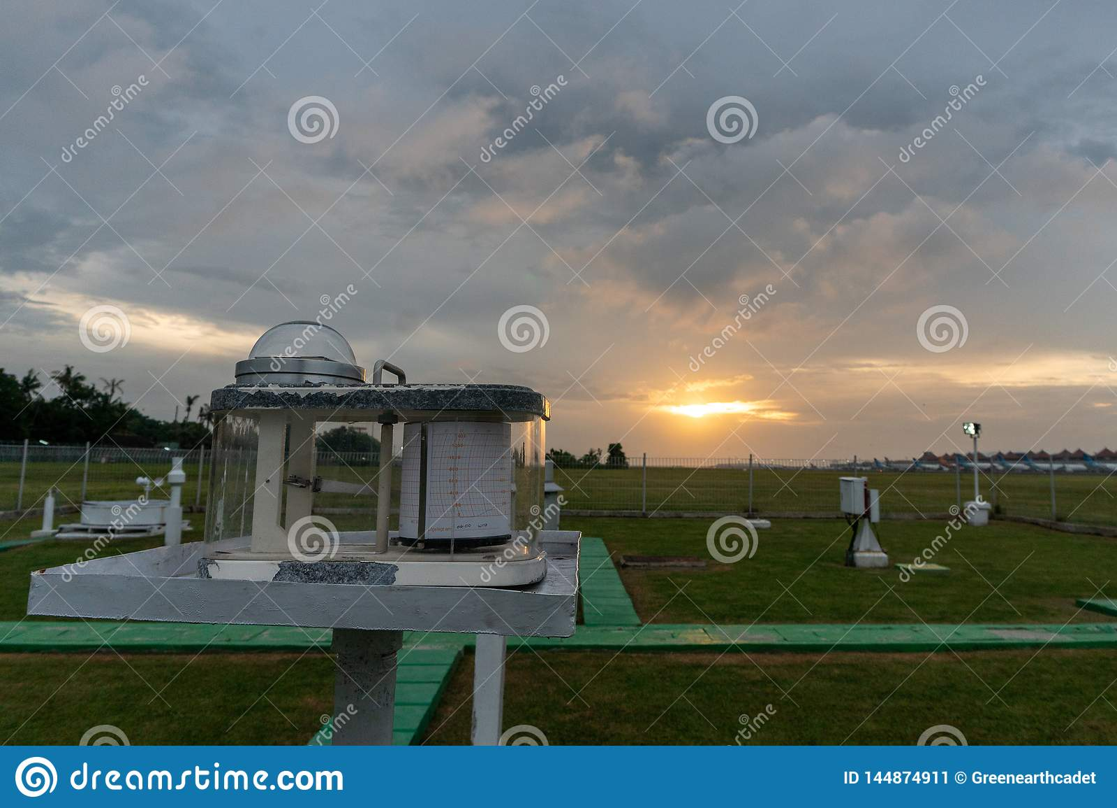 Pyranograph на поле метеорологии с зеленой травой и когда заход солнца под о