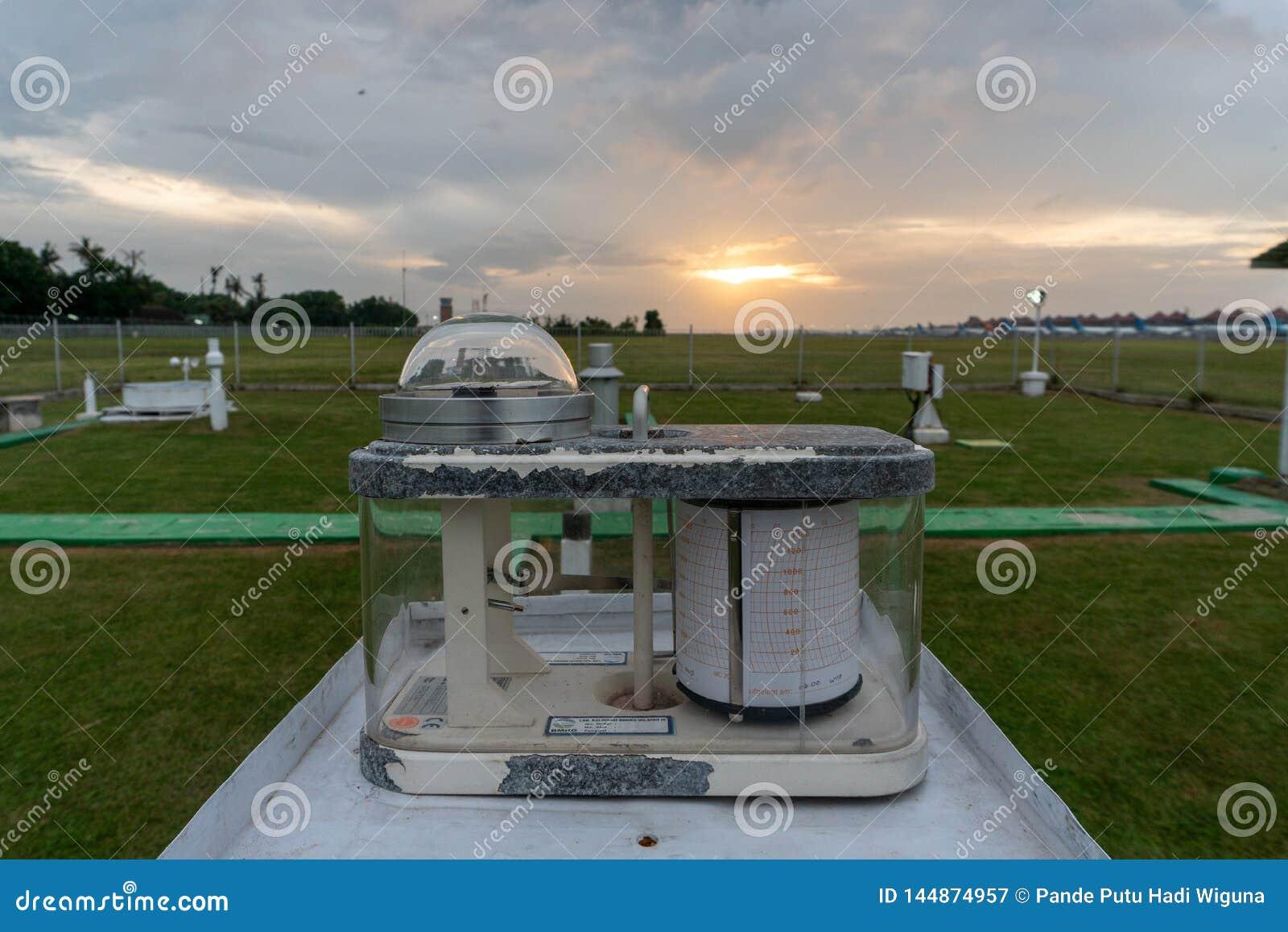 Pyranograph en el campo de la meteorología con la hierba verde y cuando puesta del sol debajo del cielo nublado