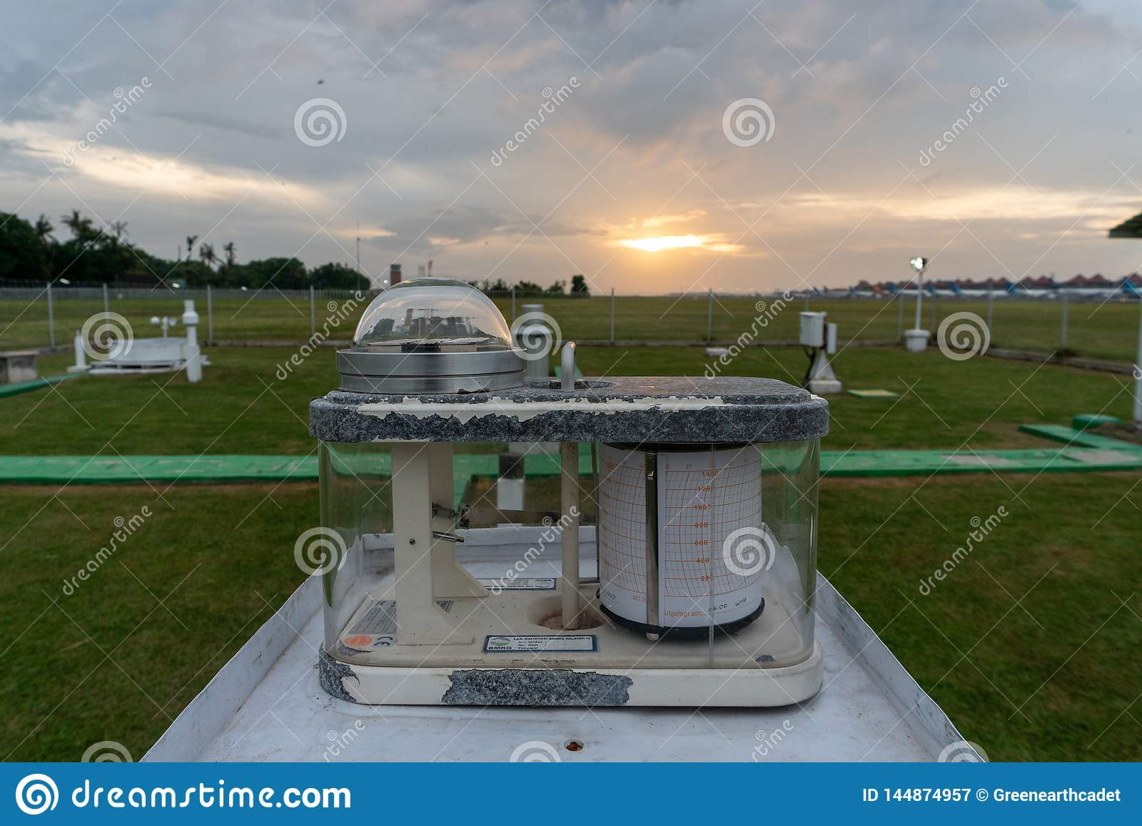 Pyranograph på meteorologifältet med grönt gräs och när solnedgång under molnig himmel