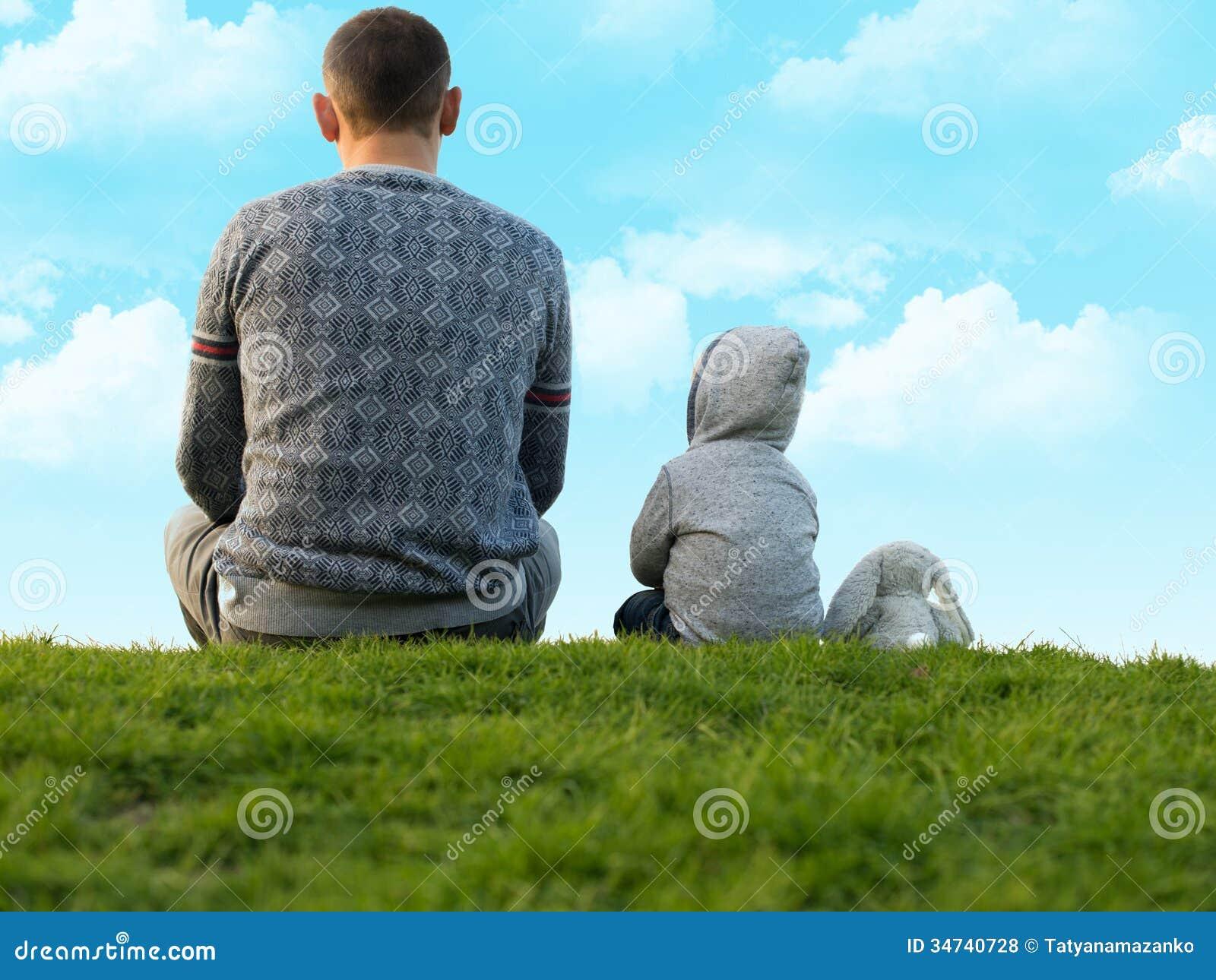 Pys med hans fader på det gröna gräset