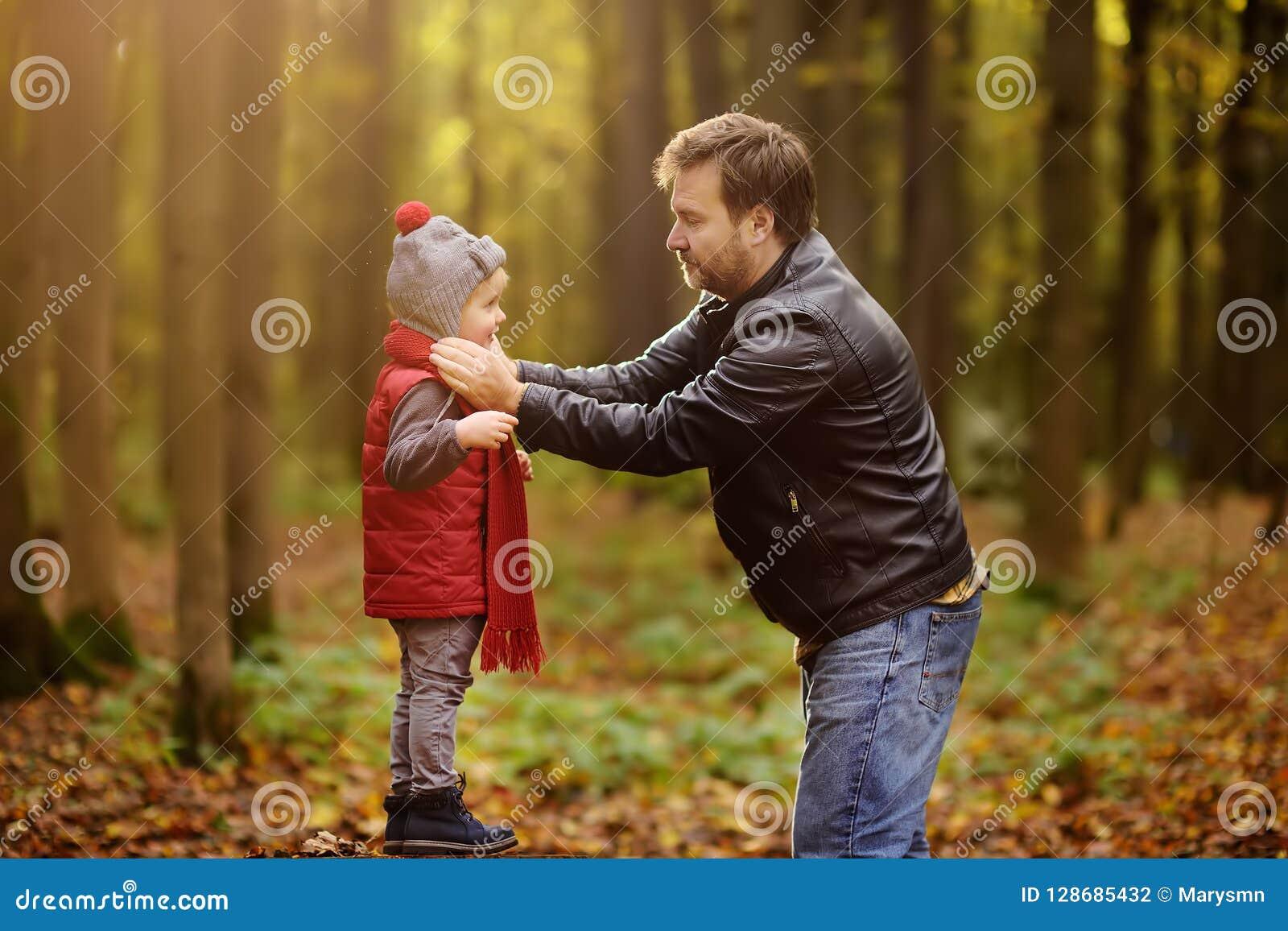 Pys med hans fader under promenad i skogen