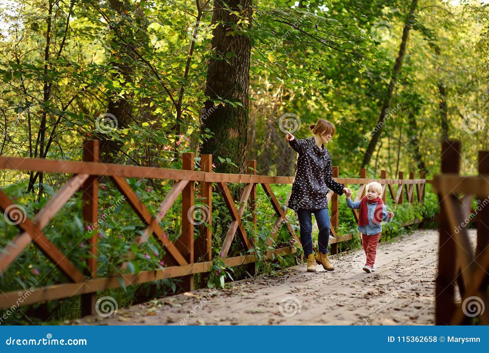 Pys med hans unga moder som talar under promenad i skogen