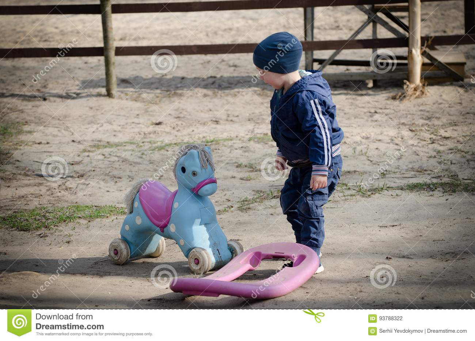 Pys och en leksakhäst på bakgrunden av en häck