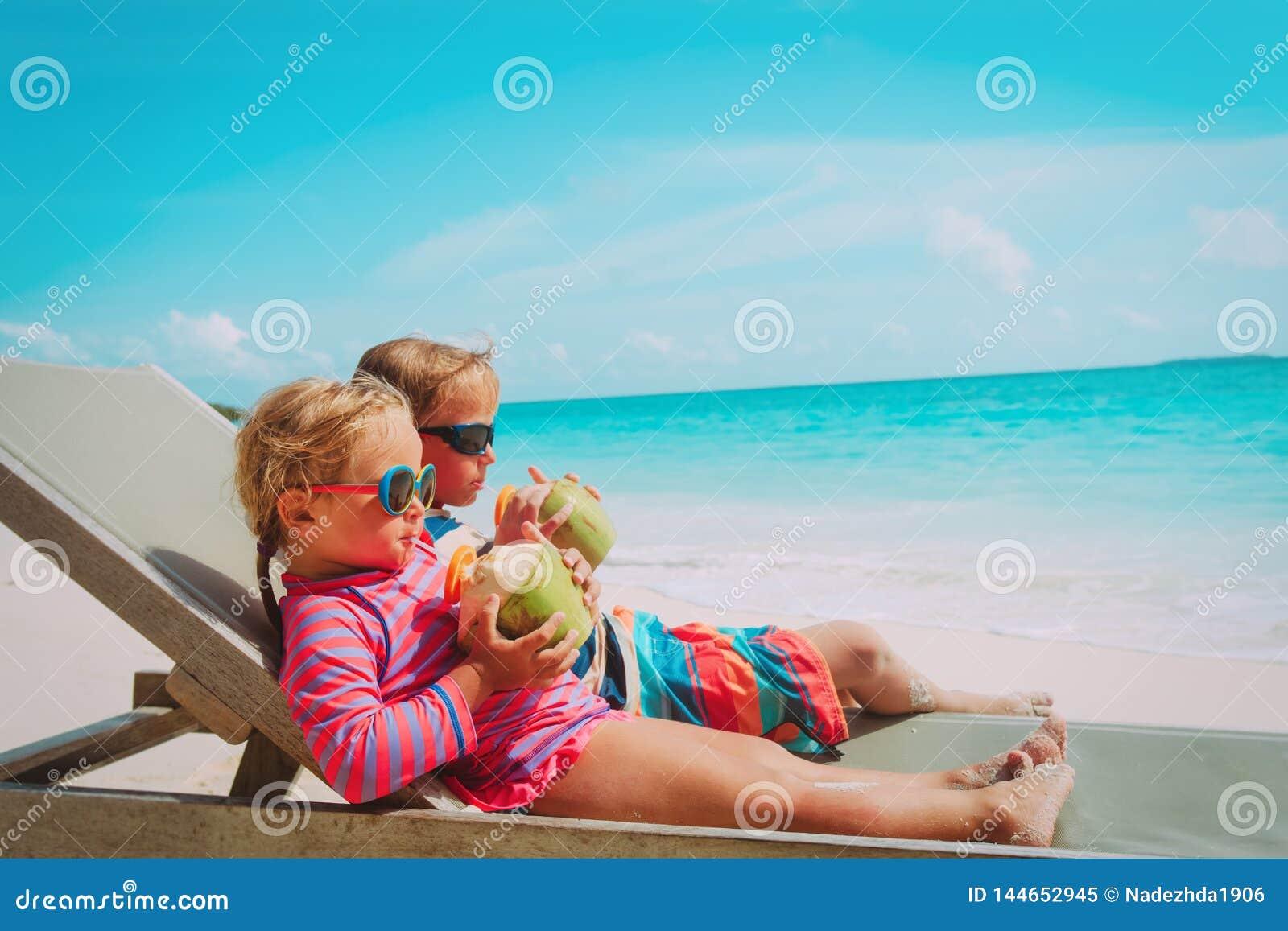 Pys och flicka som dricker kokosnöten på strandsemester